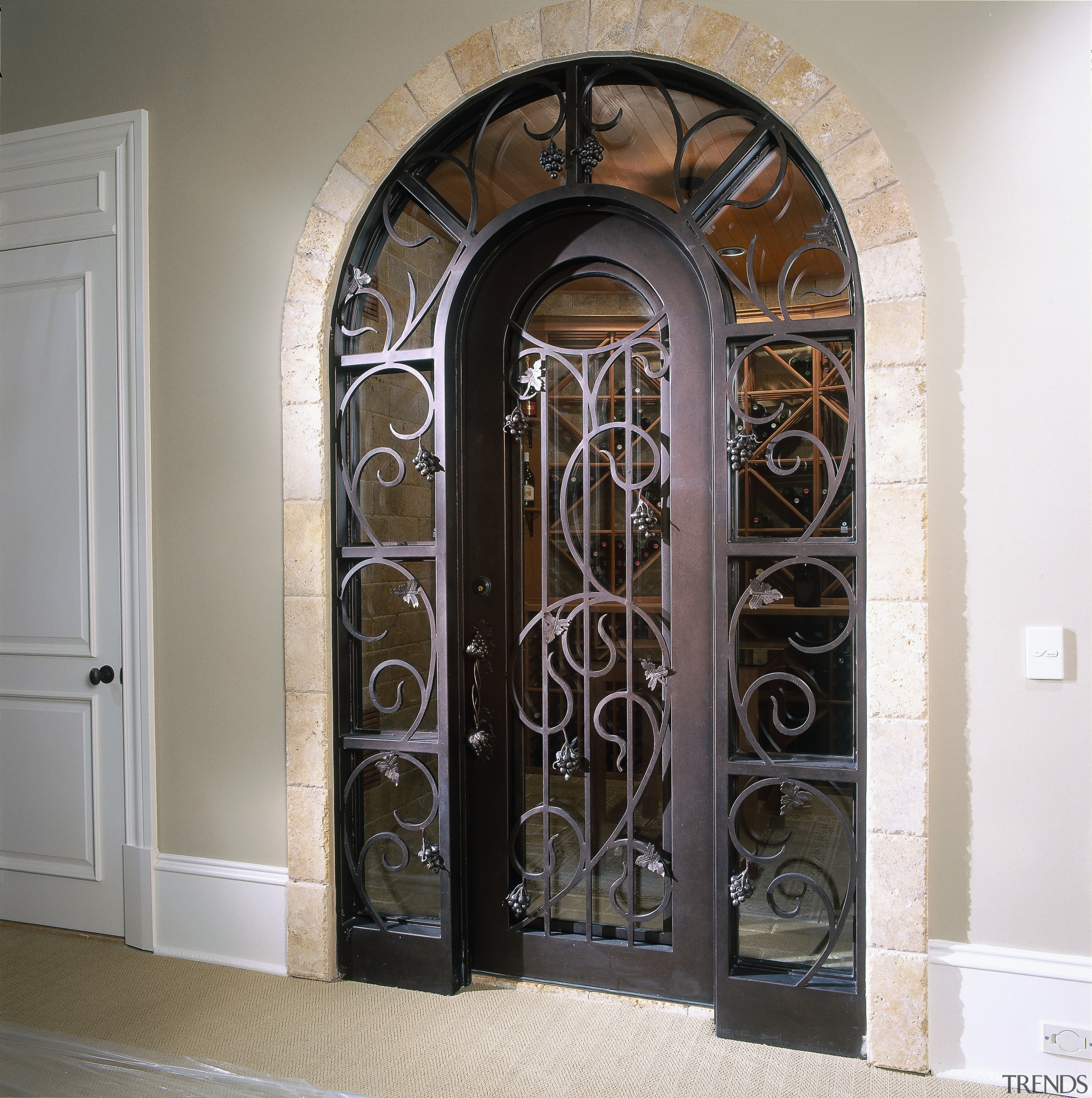 View of the entrance to the wine cellar arch, door, iron, window, white, gray, black