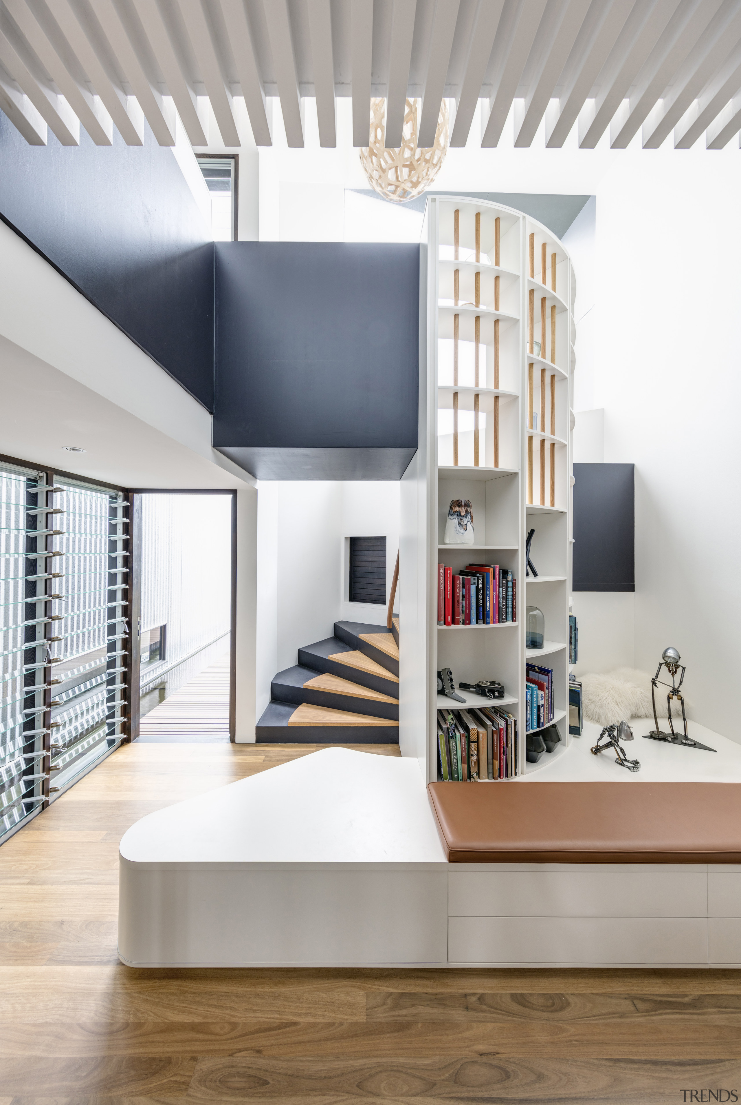 The spiral staircase in this family home by home, house, bookcase, design, floor, flooring, furniture, home, house, interior design, living room, shelf, shelving, space, stairs, CplusC Architectural Workshop