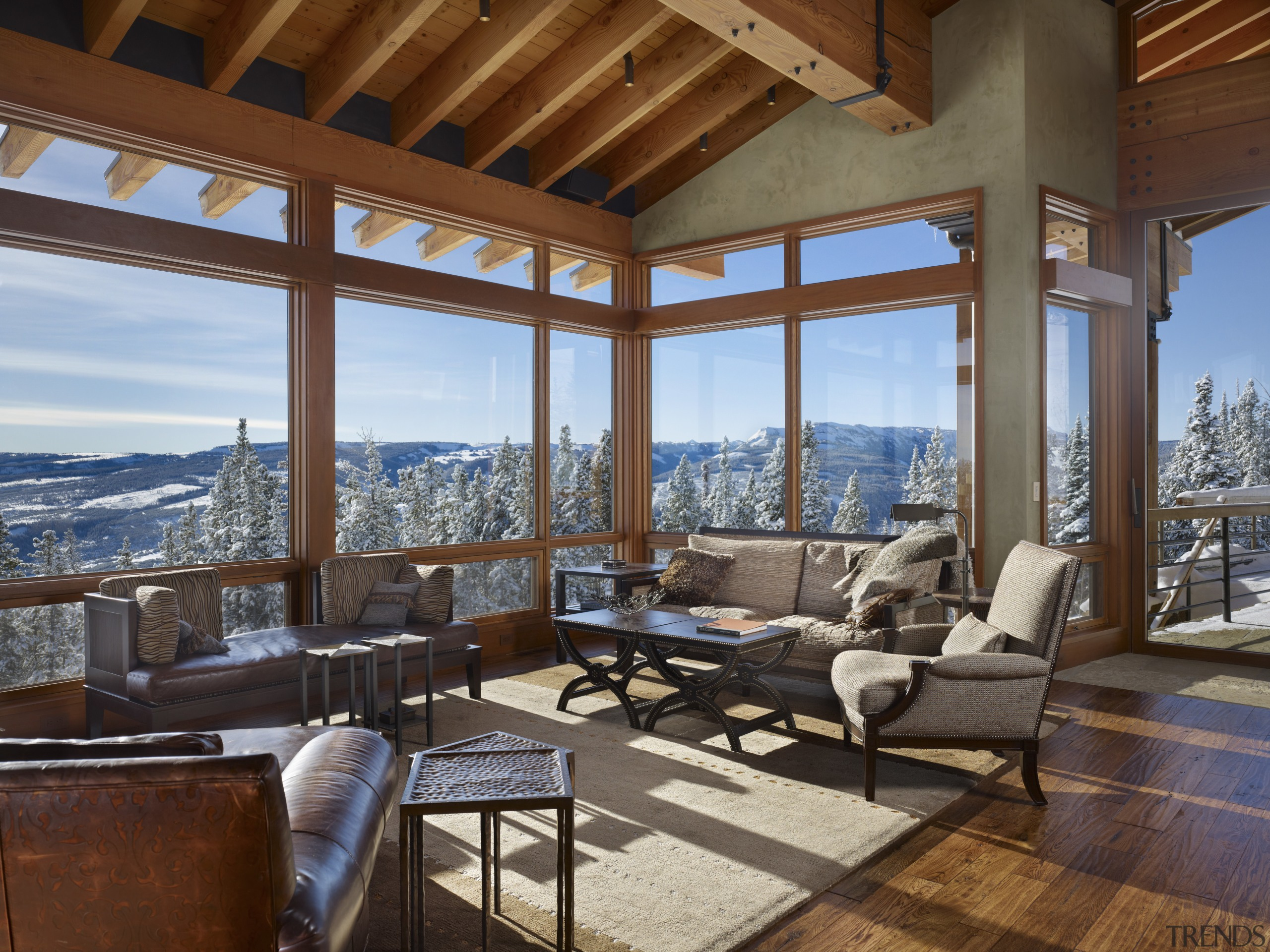 The sitting room in this mountain house is estate, home, interior design, living room, outdoor structure, penthouse apartment, porch, property, real estate, window, wood, brown