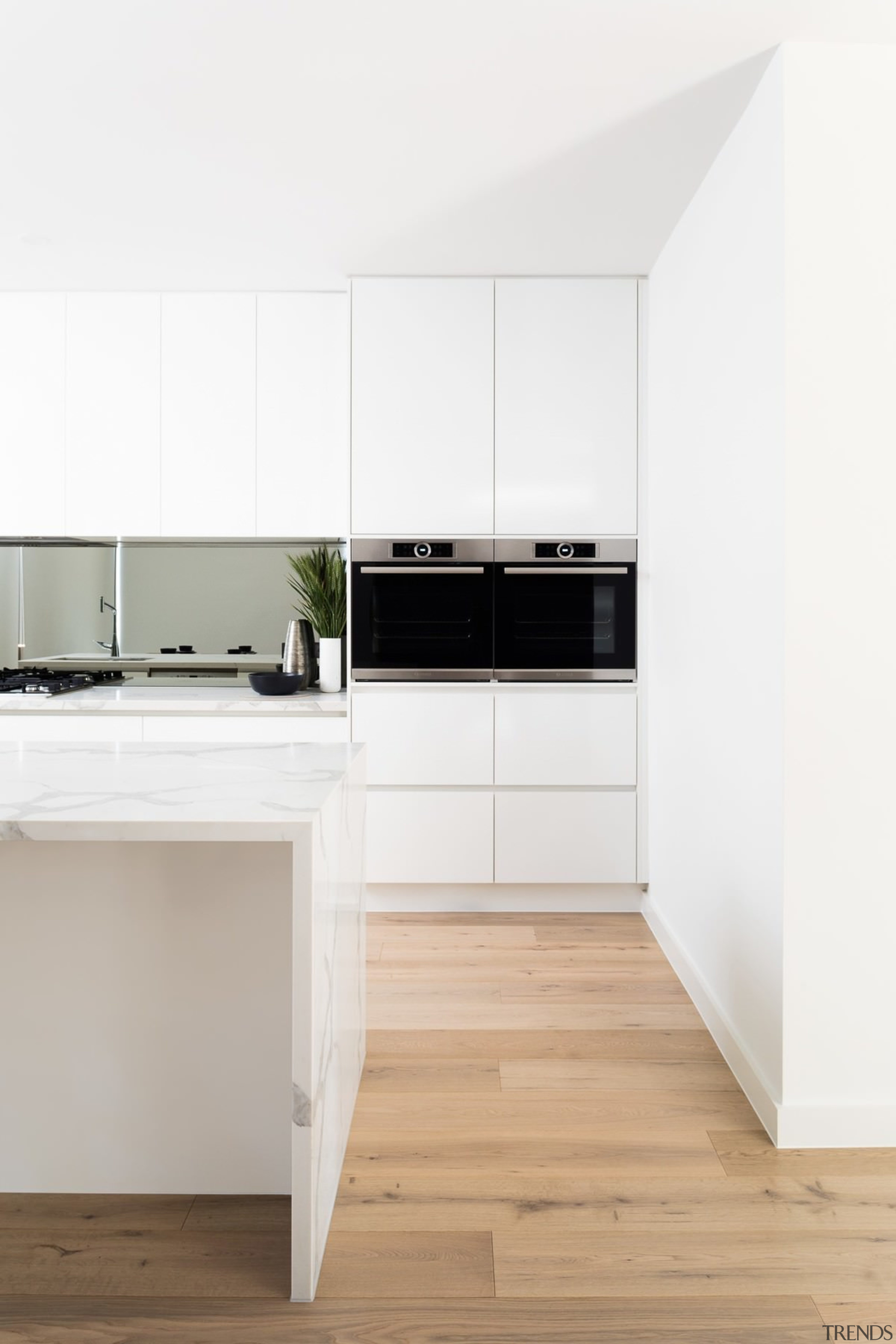 Furthering a theme of symmetry found throughout parts angle, countertop, floor, flooring, interior design, kitchen, laminate flooring, product, product design, wood flooring, white