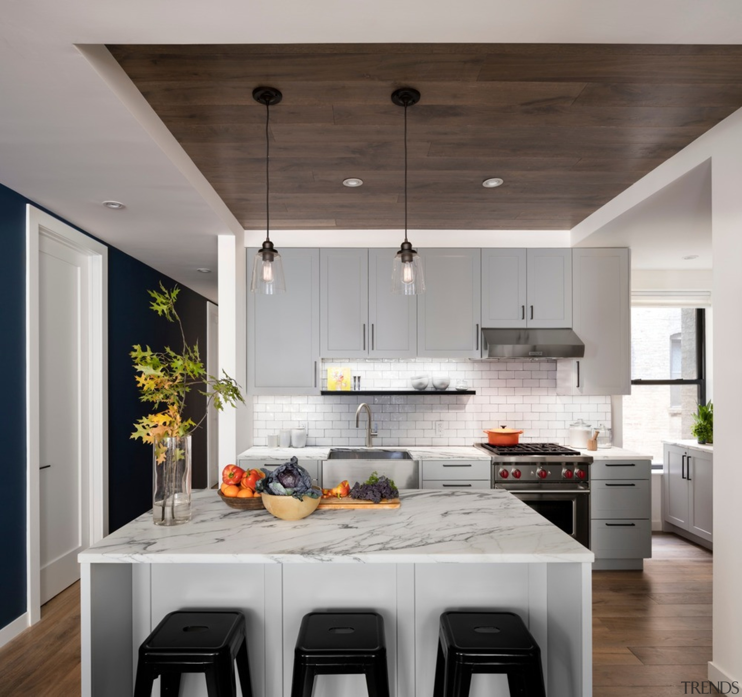 Semicustom kitchen cabinets and statuarietto marble countertops with architecture, building, cabinetry, ceiling, countertop, cuisine classique, cupboard, dining room, floor, flooring, furniture, hardwood, home, house, interior design, kitchen, kitchen stove, light fixture, major appliance, material property, property, room, table, white, wood flooring, gray