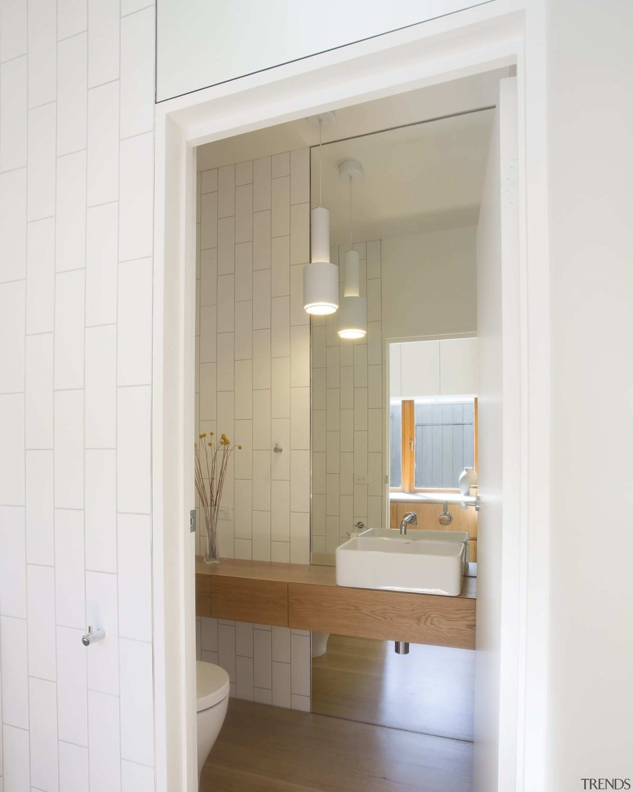 This powder room tucked off to the side, bathroom, bathroom accessory, bathroom cabinet, door, floor, home, interior design, plumbing fixture, room, sink, window, white