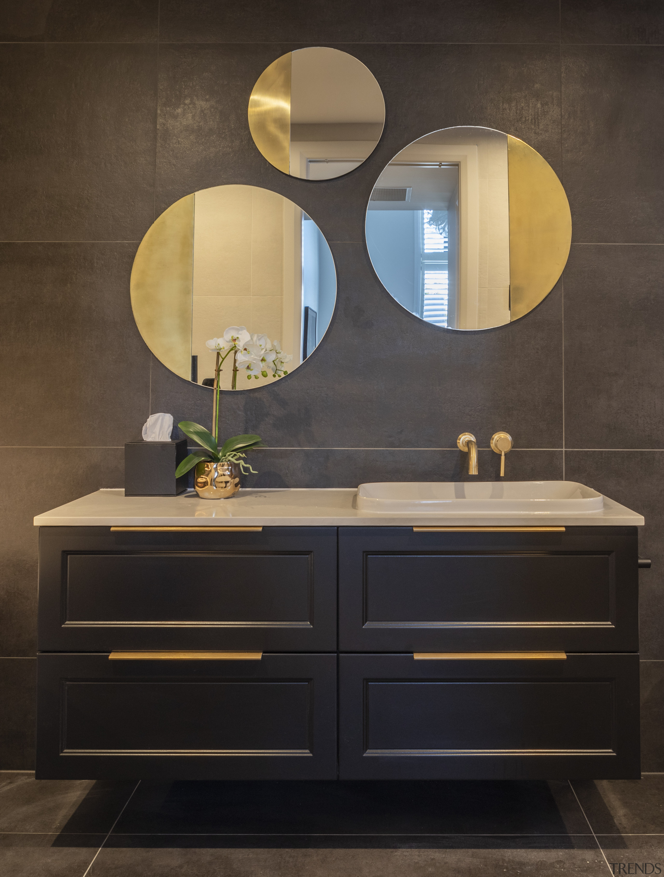 ​​​​​​​This custom, floating vanity has polished brass handles black