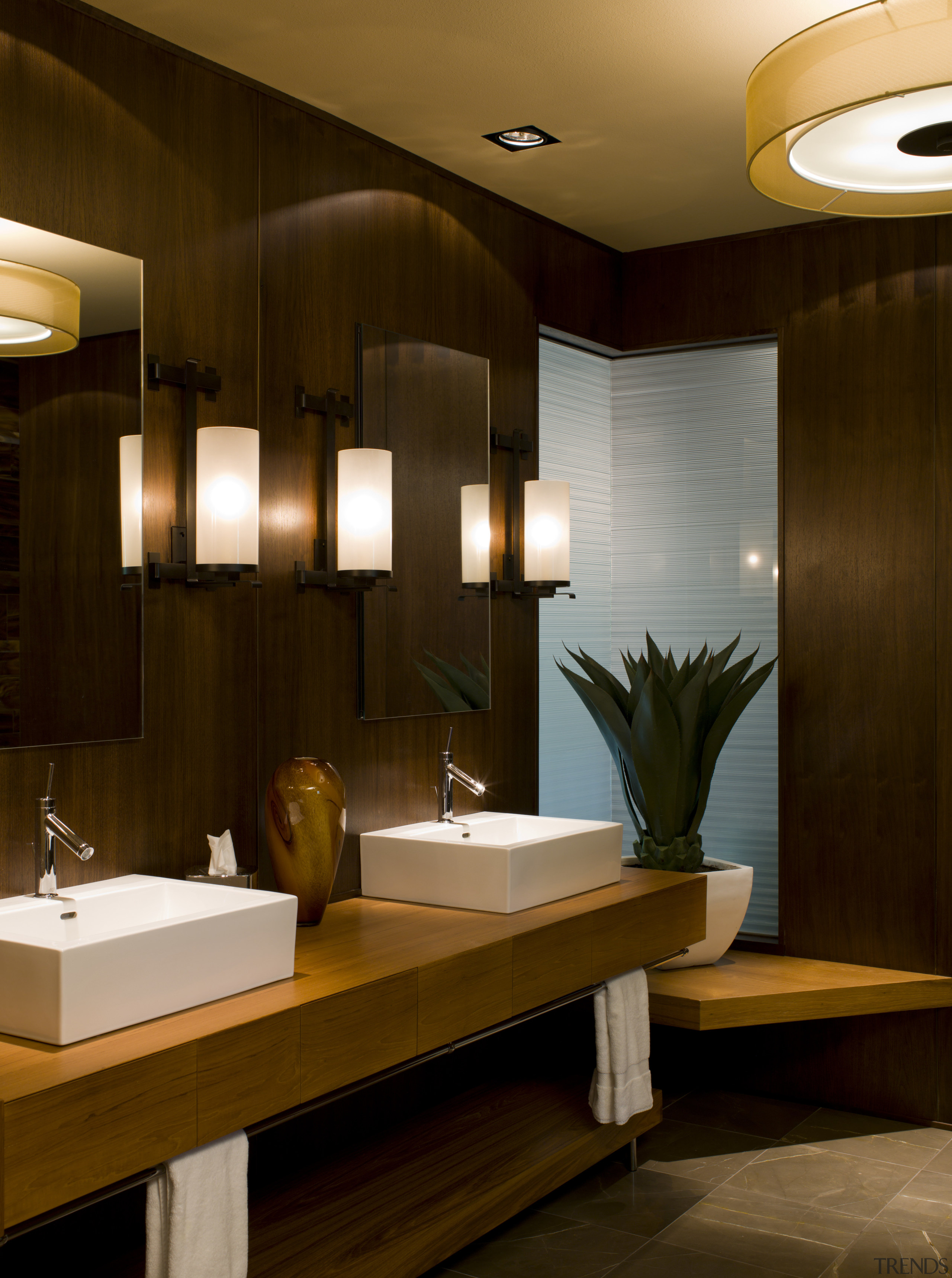 Walnut paneling in this bathroom matches the walls in the adjoining hallway. A new corner window allows borrowed light to travel in both directions.