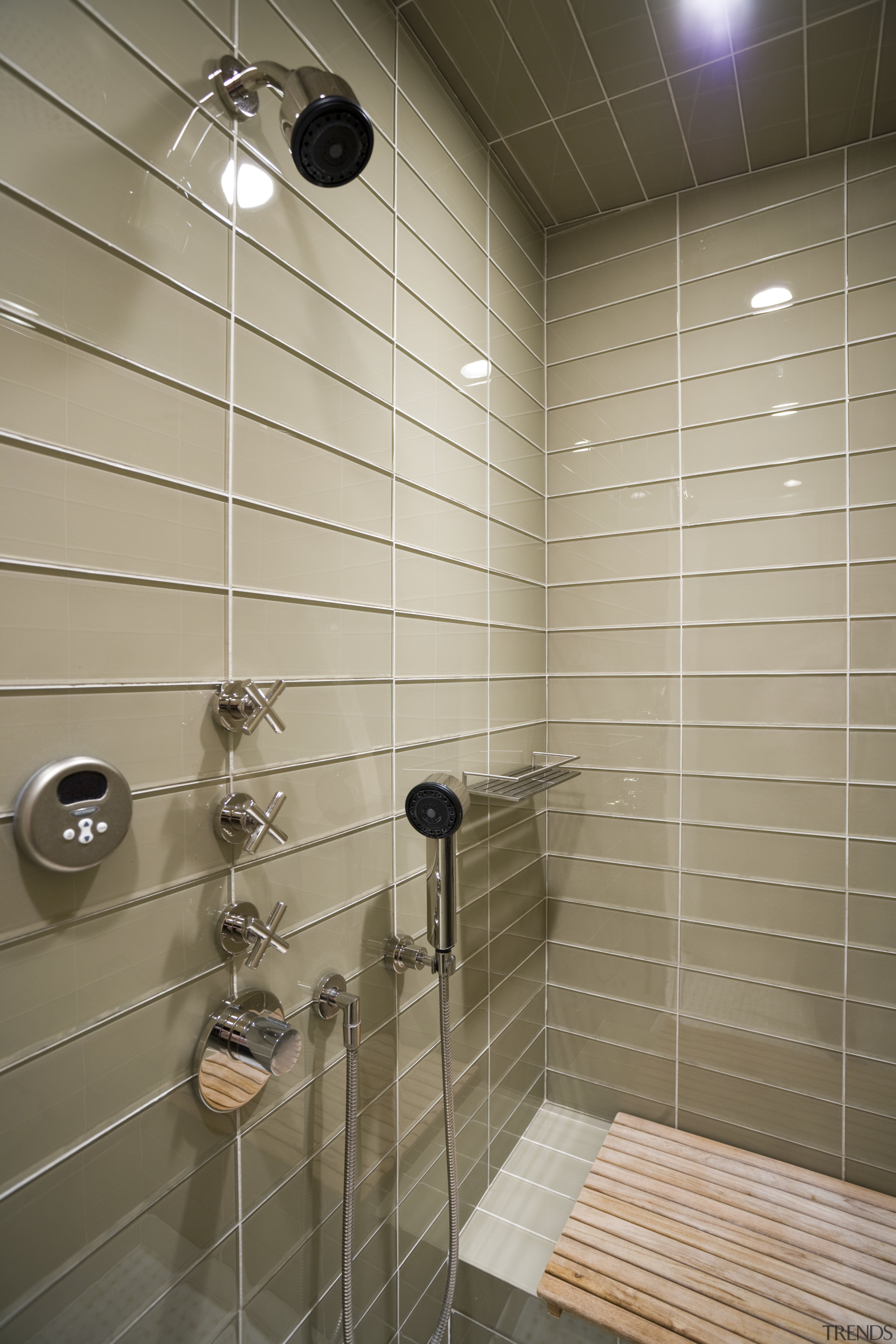 View of shower enclosure which features wall tiling, bathroom, floor, flooring, interior design, plumbing fixture, room, shower, tile, wall, gray, brown