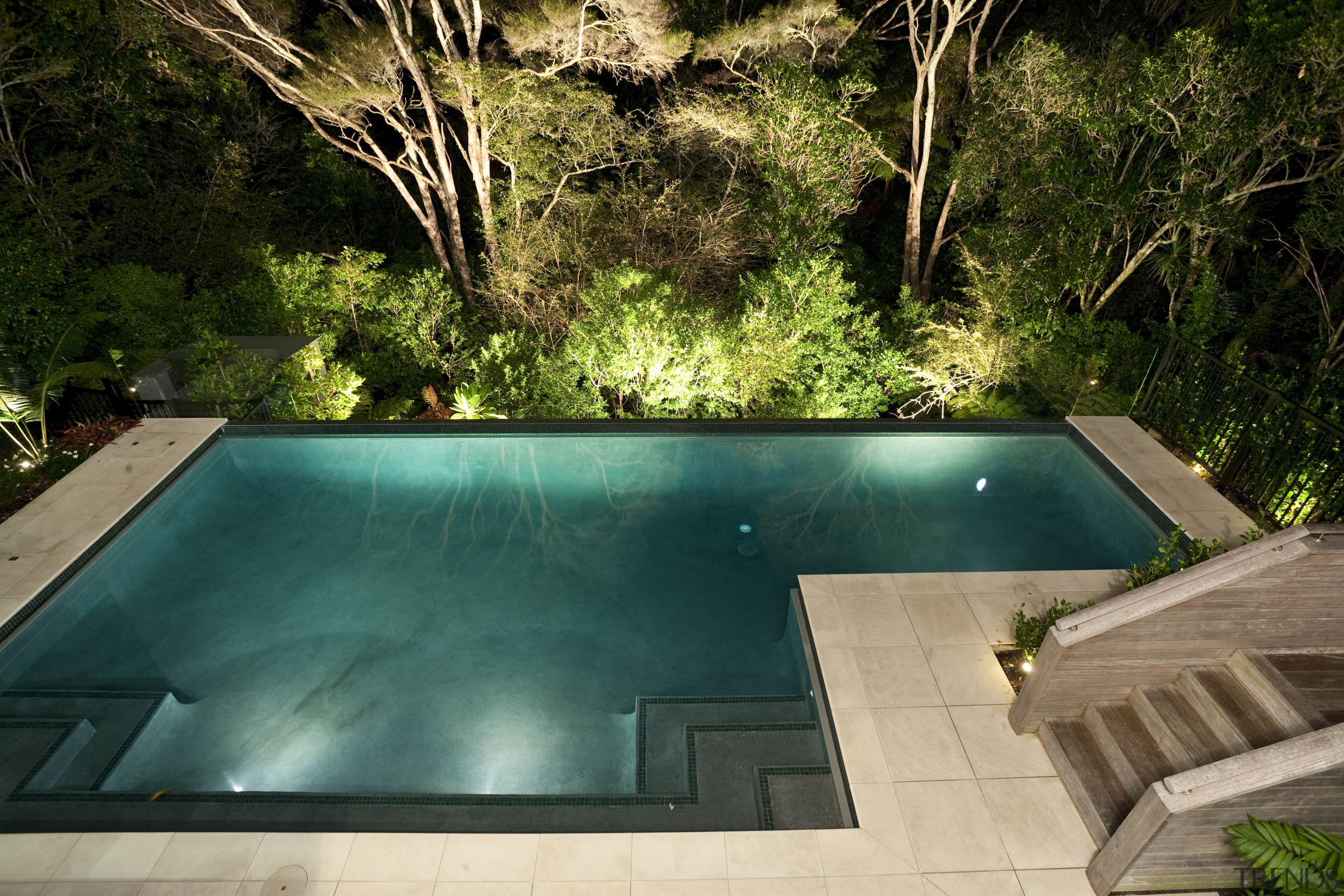 View of sleek poolscape with textured stone wall, backyard, estate, leisure, lighting, plant, property, real estate, swimming pool, water, yard, brown