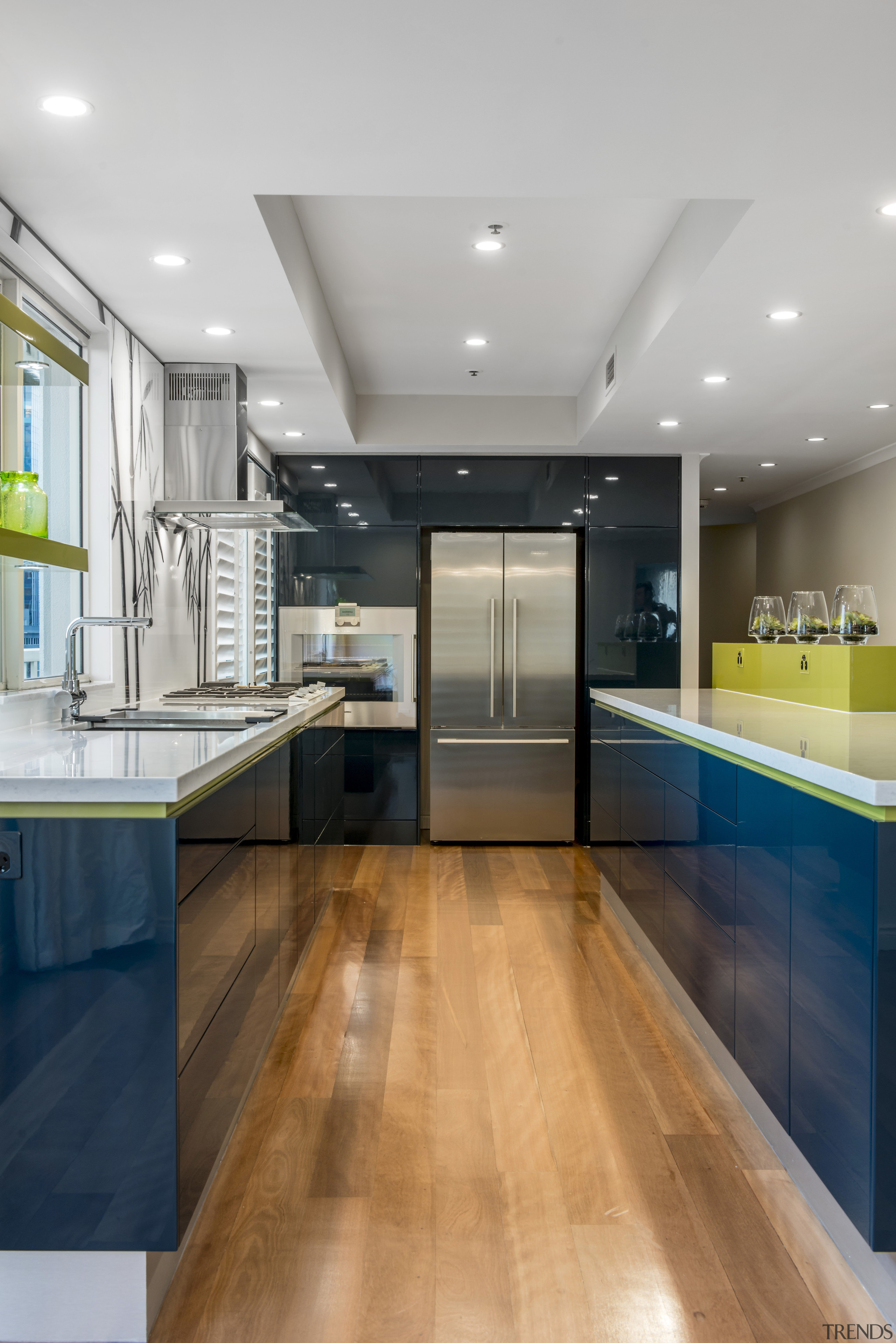 This two-tone design celebrates connections and contrast. The cabinetry, ceiling, countertop, floor, flooring, hardwood, house, interior design, kitchen, real estate, room, wood flooring, gray