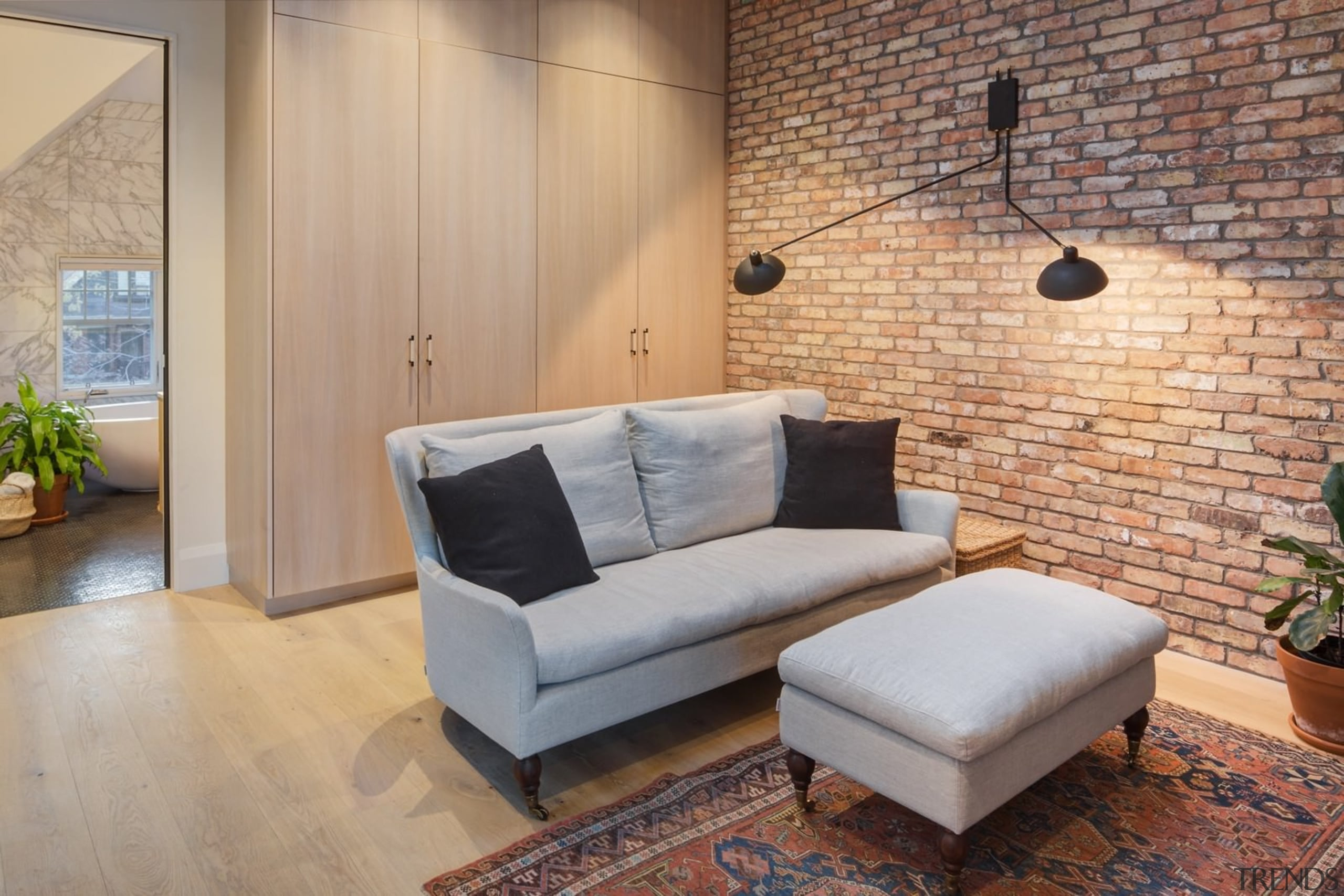 Another view of the brick feature wall and ceiling, couch, floor, flooring, furniture, hardwood, home, interior design, living room, loft, property, real estate, room, wall, wood, wood flooring, gray, orange