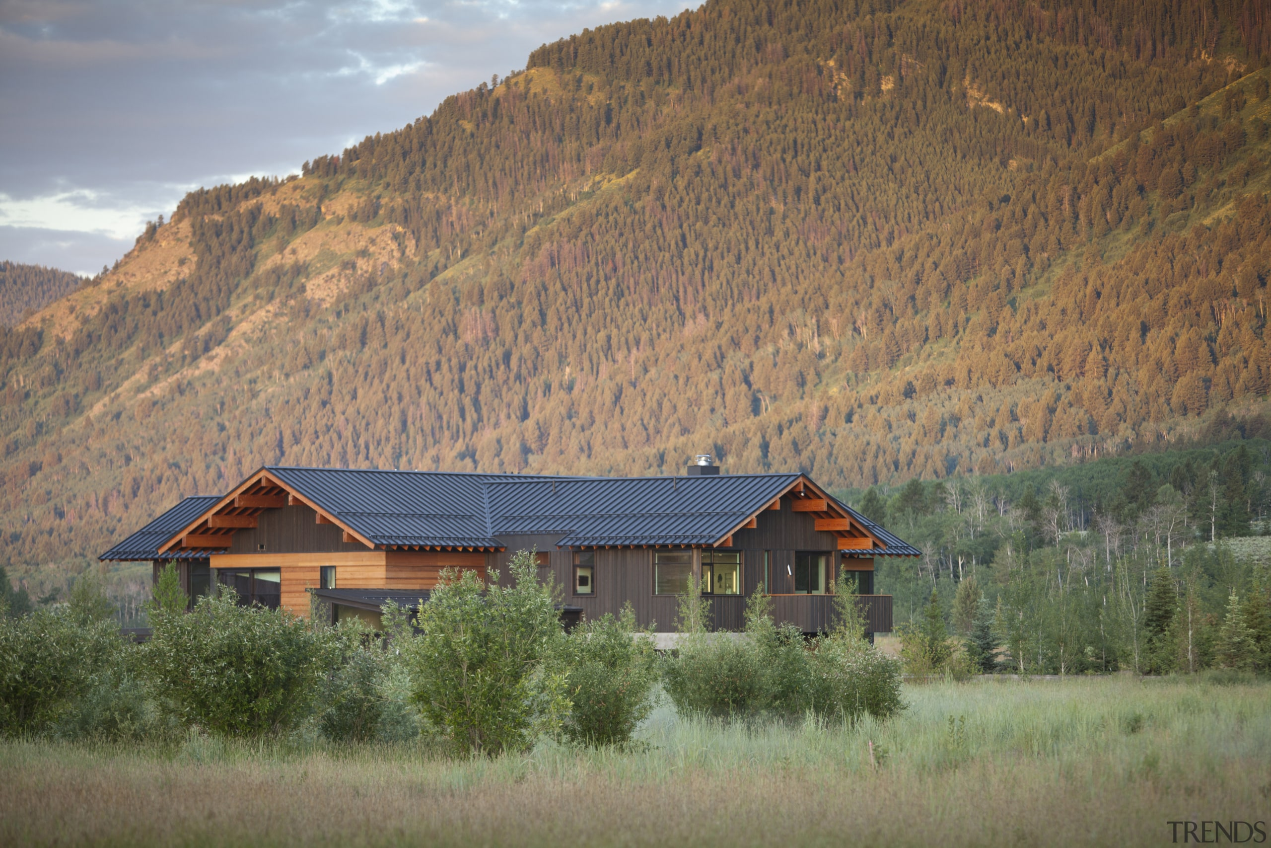 This rustic-looking mountain home by architect Stephen Dynia biome, cloud, cottage, farm, field, grassland, highland, hill, home, house, hut, landscape, log cabin, morning, mountain, mountain range, mountainous landforms, national park, nature, real estate, roof, rural area, sky, sunlight, tree, wilderness, brown