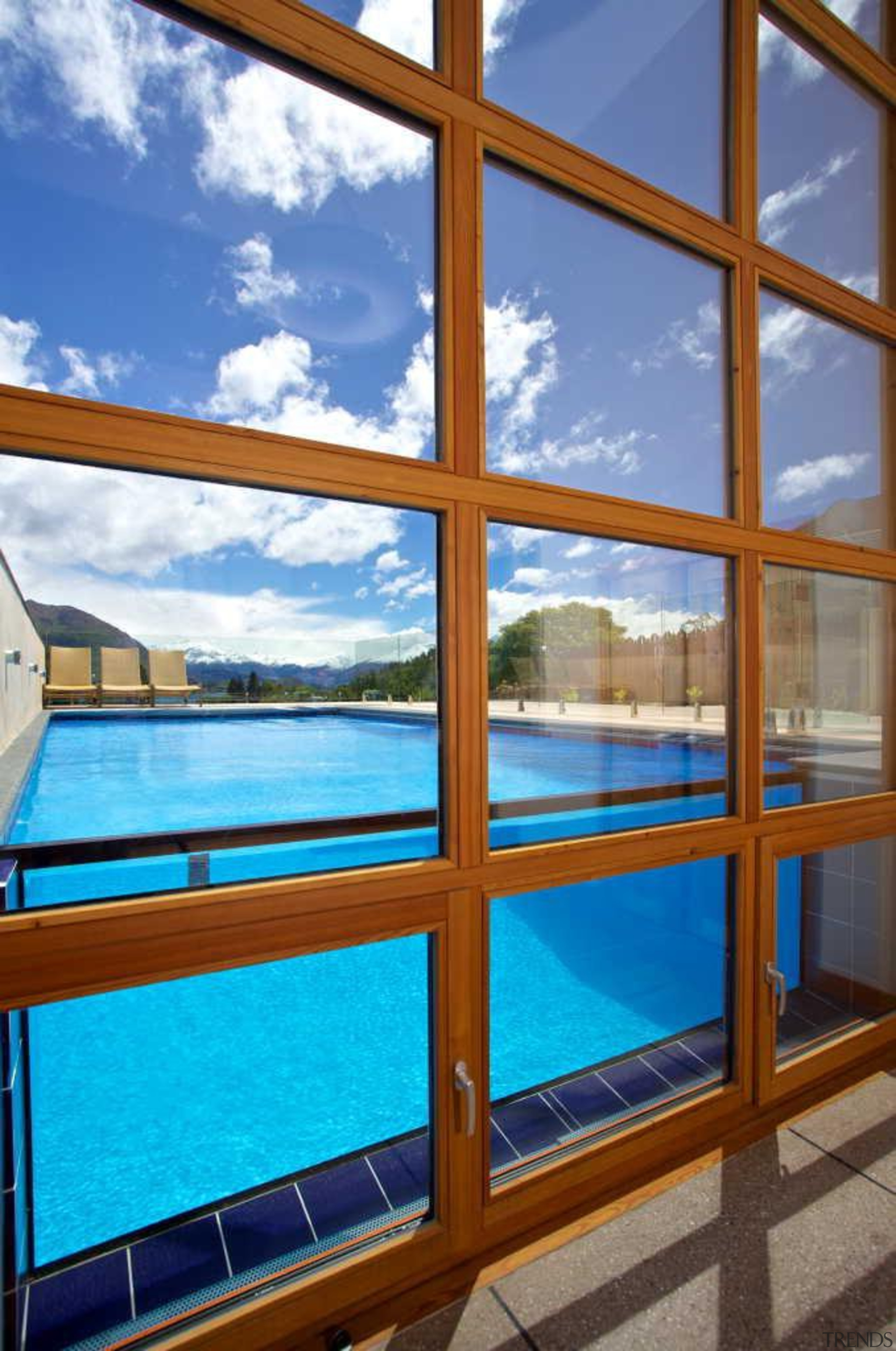 This pool by Mayfair Pools laps against the apartment, condominium, daylighting, glass, property, real estate, sky, swimming pool, window, blue