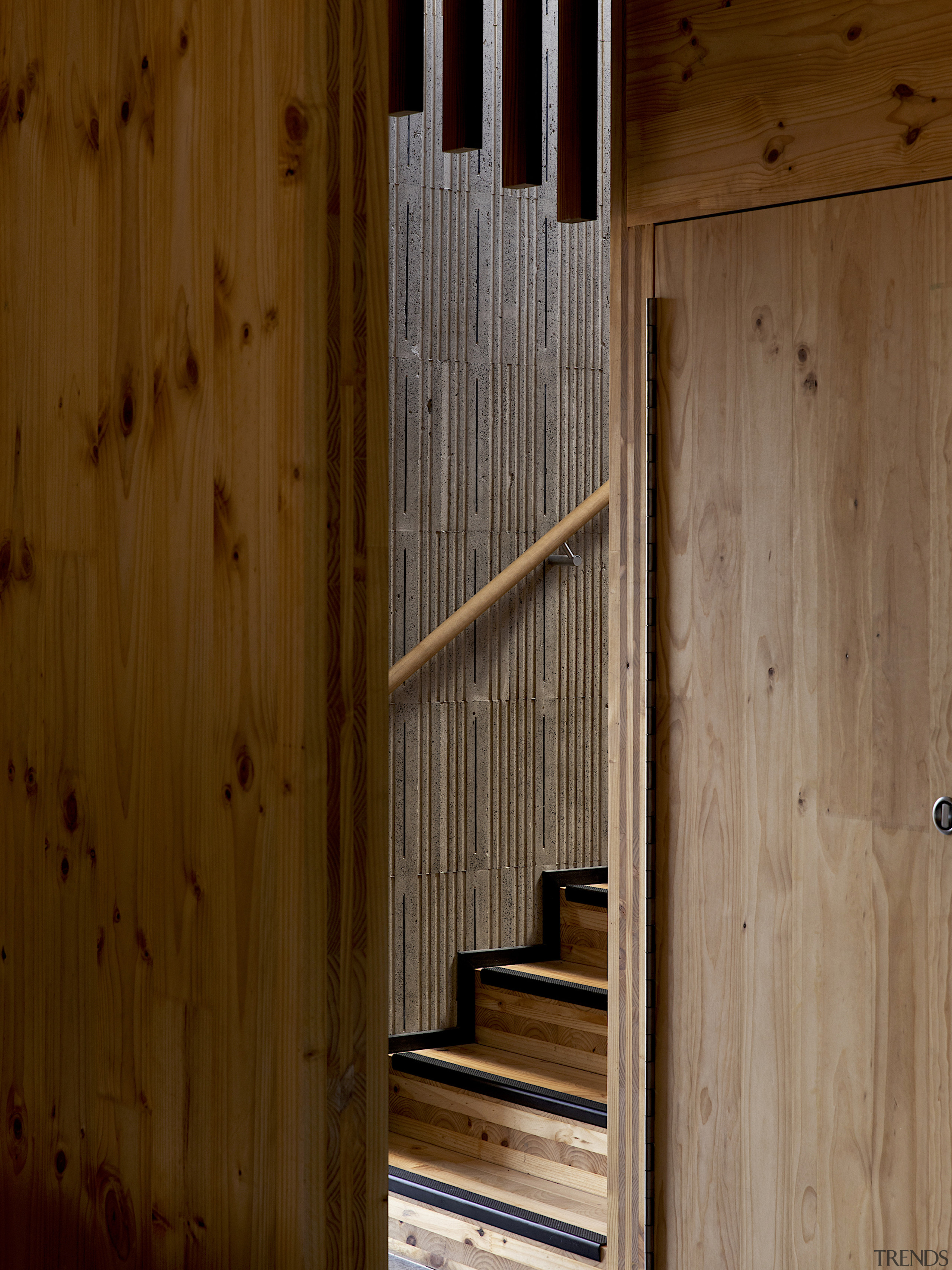 The stairwell is wrapped in concrete finished with brown