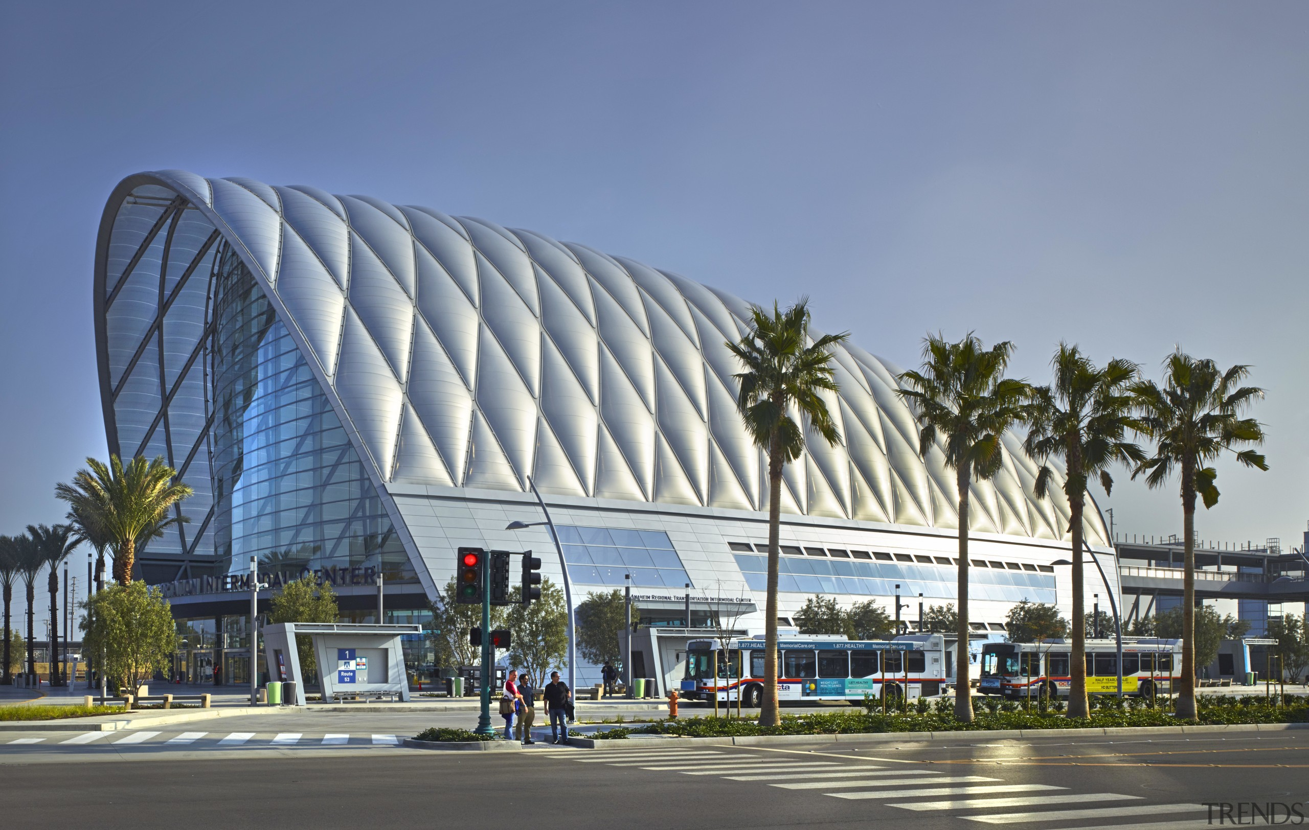 The new ARTIC transit hub in Anaheim is architecture, building, city, convention center, corporate headquarters, daytime, landmark, metropolis, metropolitan area, mixed use, palm tree, plaza, sky, structure, teal, gray