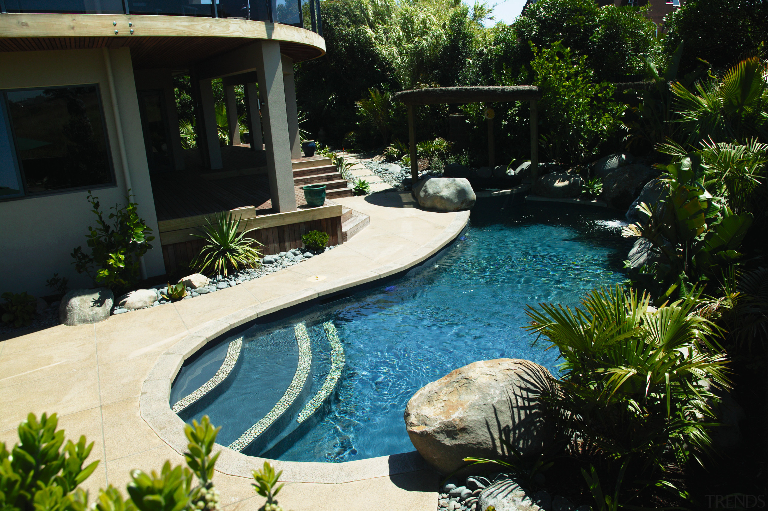 Landscaped swimming pool area with paving, boulders, plants backyard, estate, landscape, landscaping, leisure, outdoor structure, plant, property, real estate, resort, swimming pool, water, water feature, yard, black