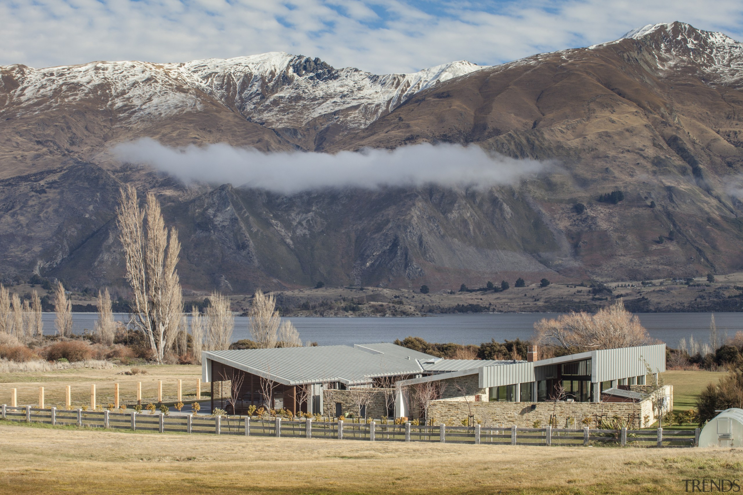This large contemporary courtyard house nestles into the alps, cloud, elevation, fell, highland, hill, landscape, mountain, mountain range, mountainous landforms, national park, ranch, rural area, sky, snow, tree, wilderness, winter, gray