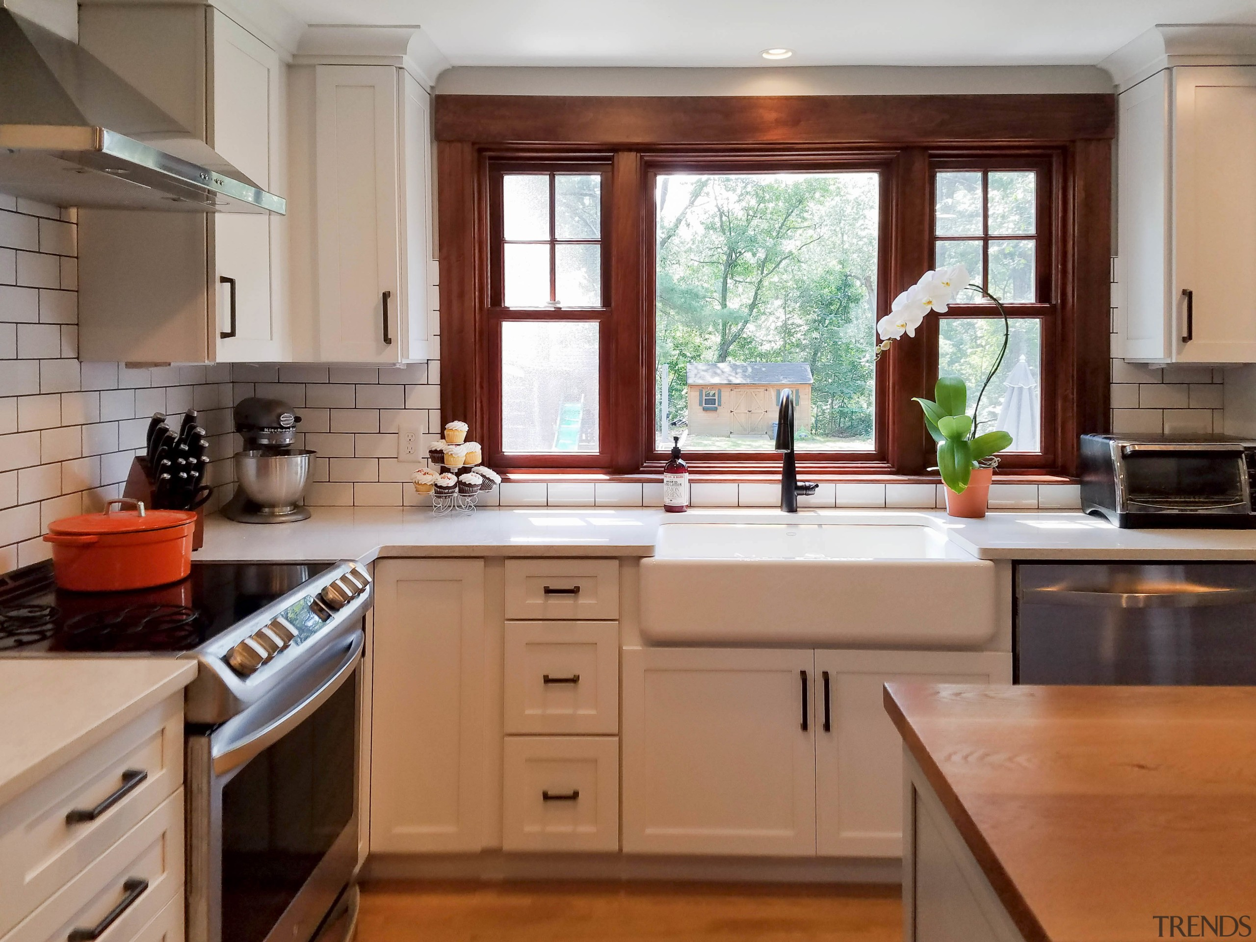 A substantial sink sits below a set of cabinetry, countertop, cuisine classique, floor, flooring, hardwood, home, interior design, kitchen, real estate, room, window, brown