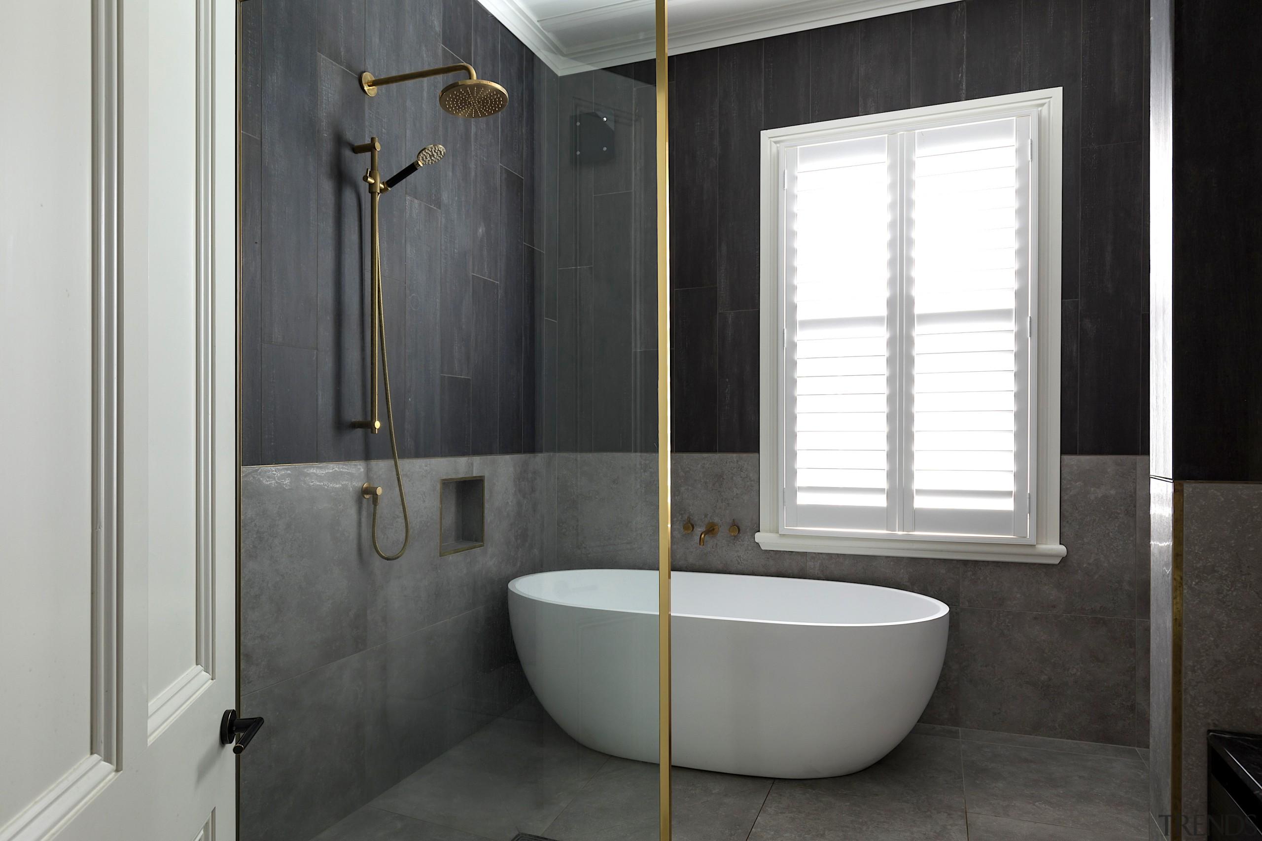 Brushed brass detailing and burnt timber-look tiles give
