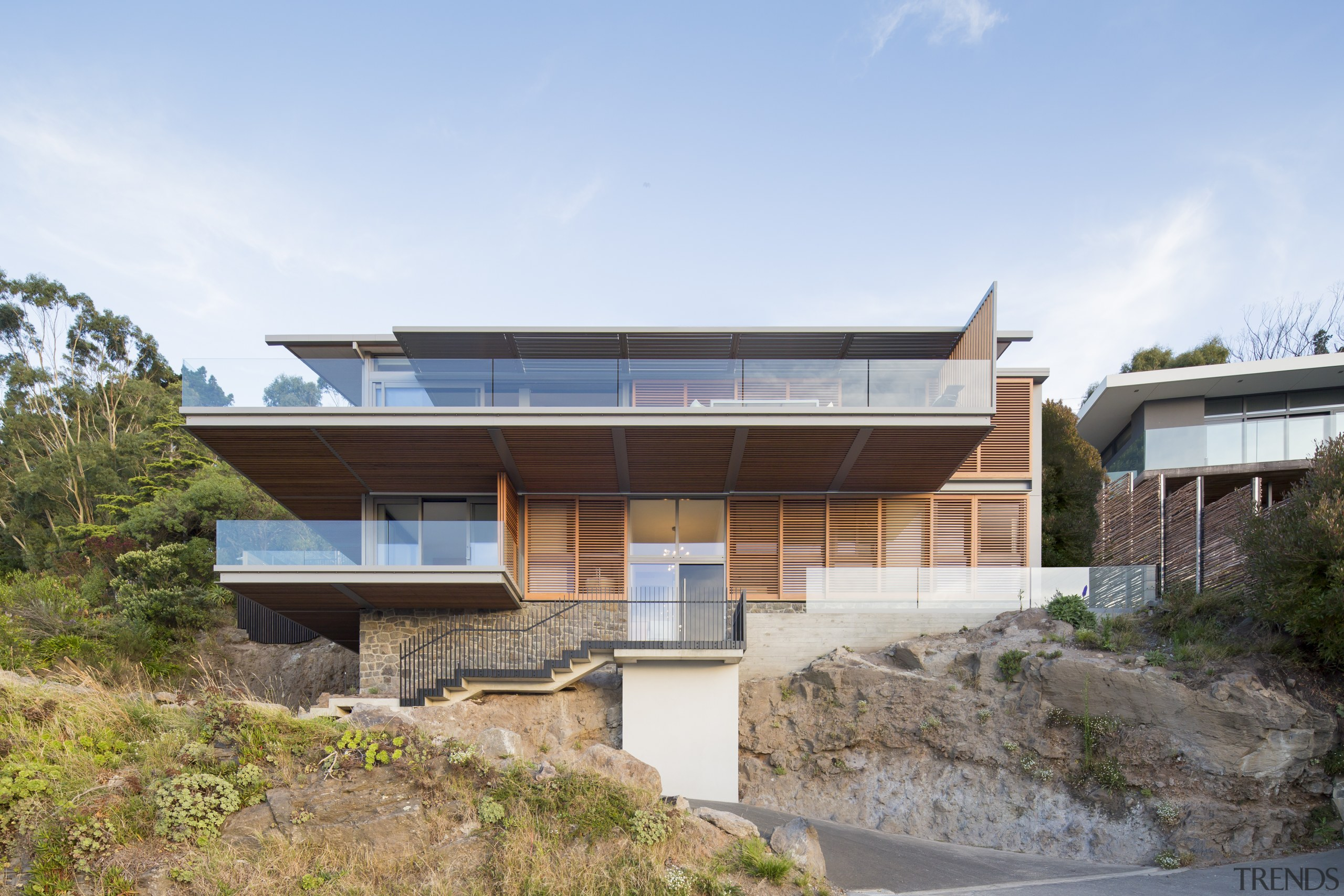 The overhanging top level of this home provides white