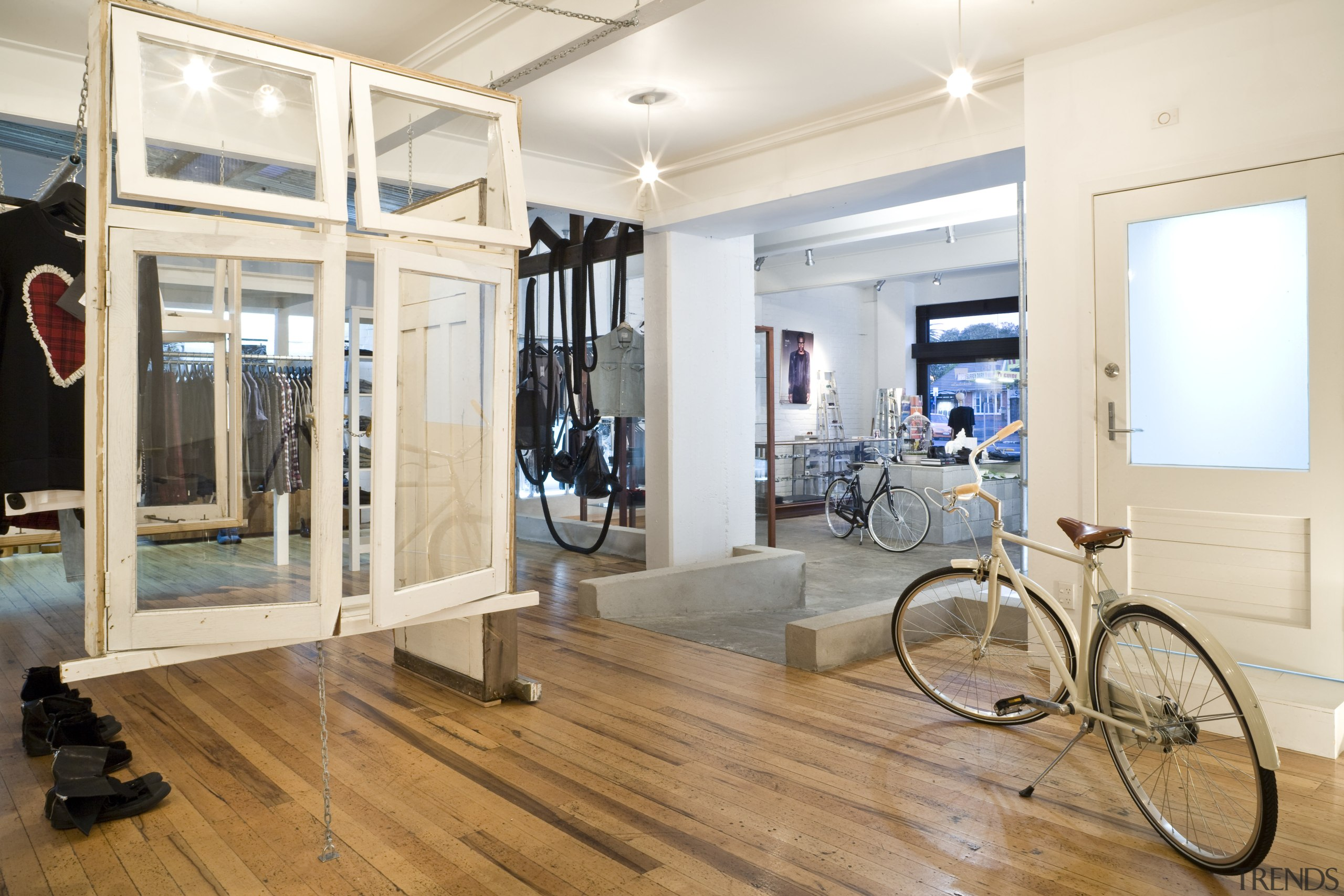 Interior view of the clothing displays at the floor, flooring, interior design, room, structure, wood, wood flooring, white
