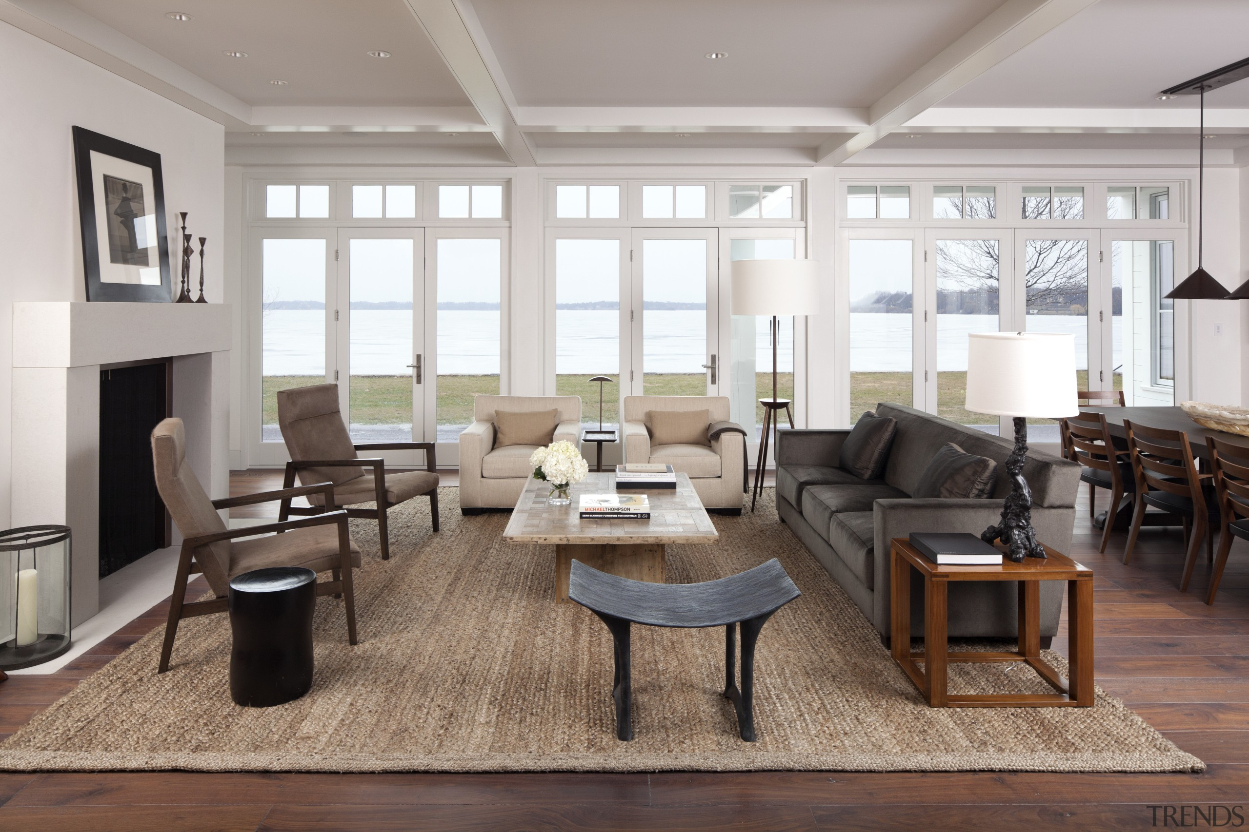 The living room of this lakefront house has chair, floor, flooring, furniture, interior design, living room, room, table, gray