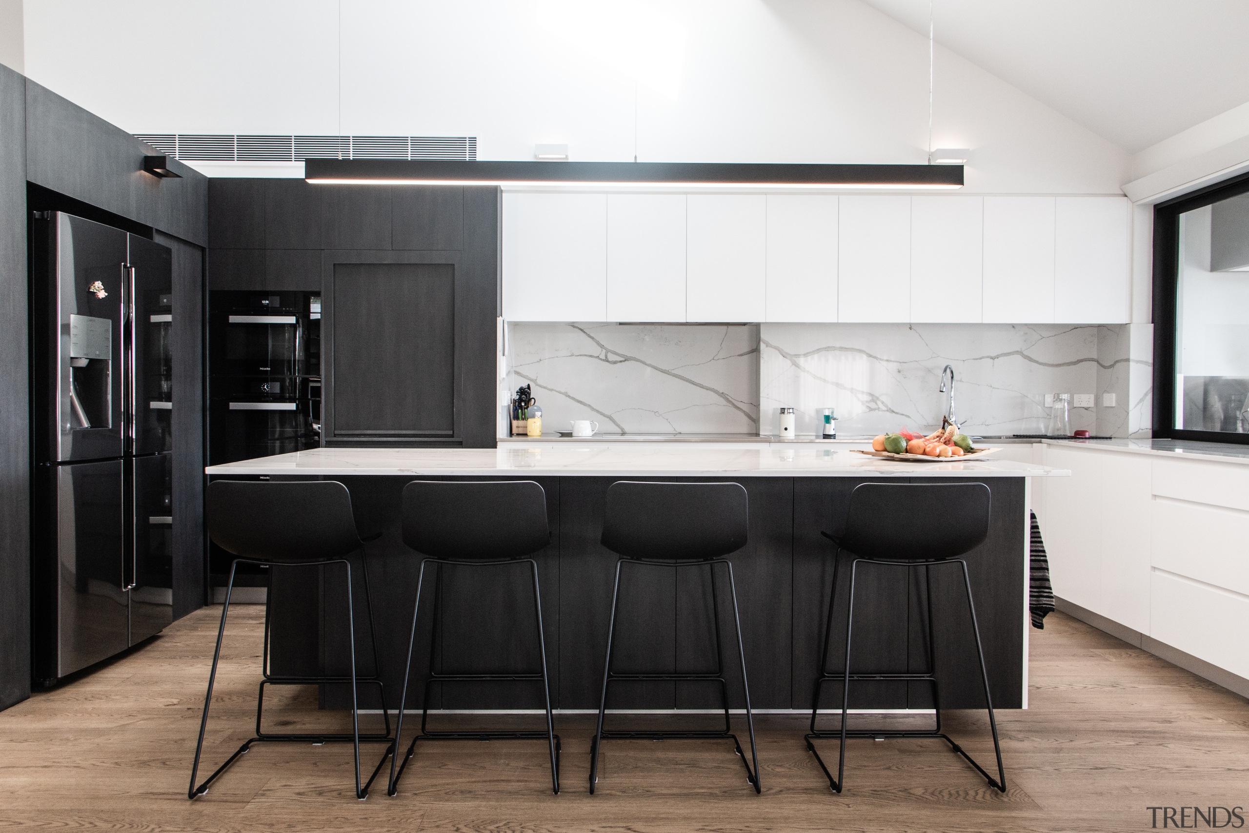 A central island provides definition and boundaries between architecture, black-and-white, building, cabinetry, ceiling, countertop, cupboard, design, dining room, floor, flooring, furniture, home, house, interior design, kitchen, kitchen stove, loft, material property, property, real estate, room, table, white, black