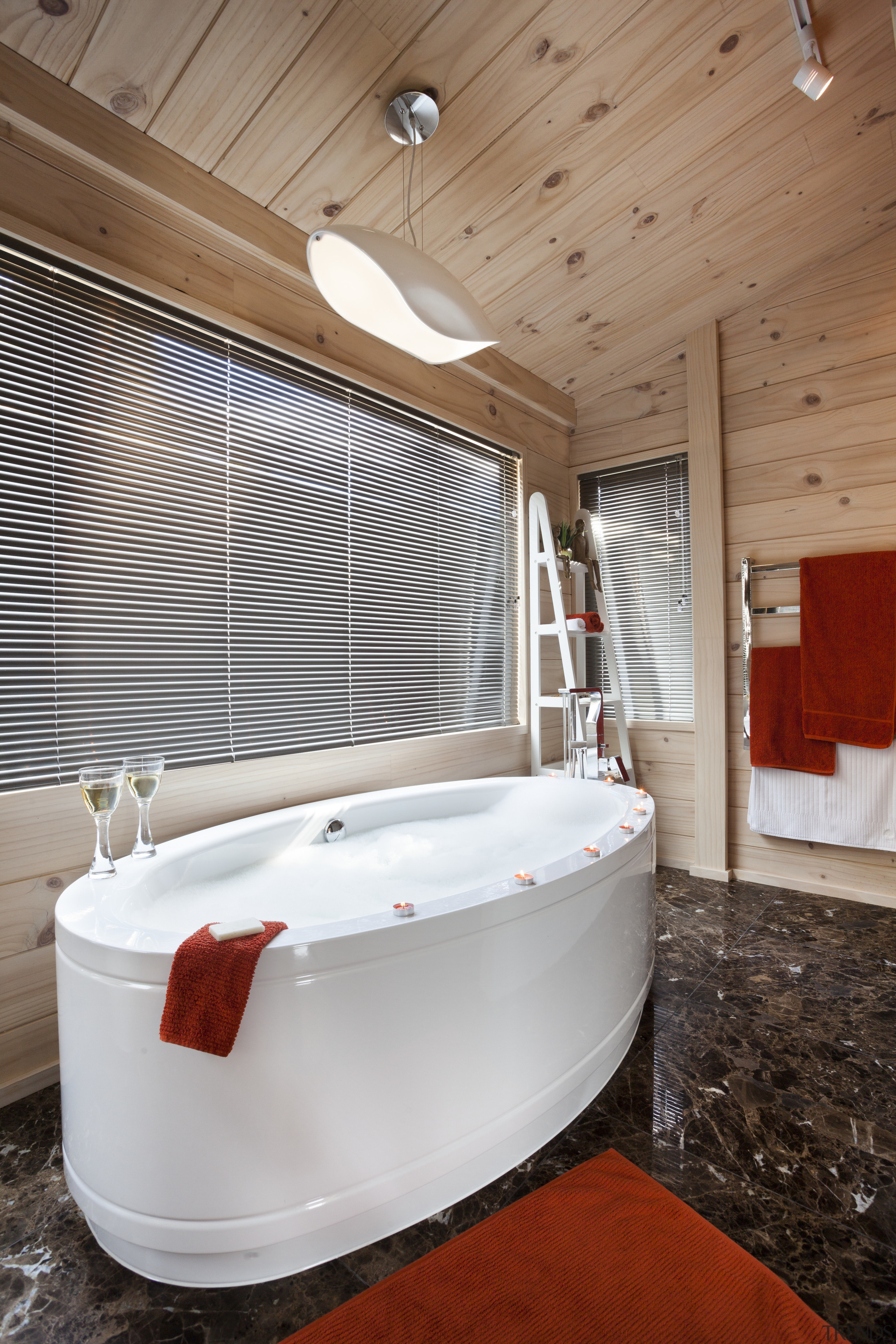 A freestanding tub is a feature of the architecture, floor, flooring, furniture, interior design, room, wood