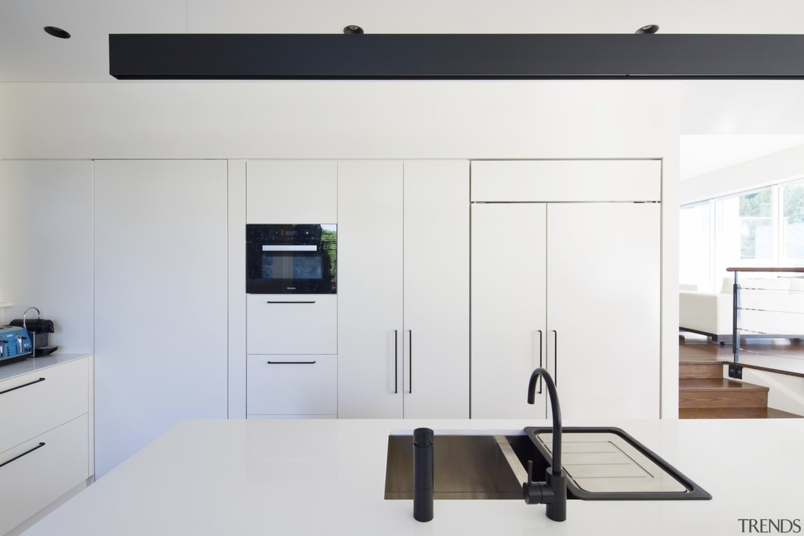 This kitchen features black tapware, which stands out home appliance, interior design, product design, white, gray