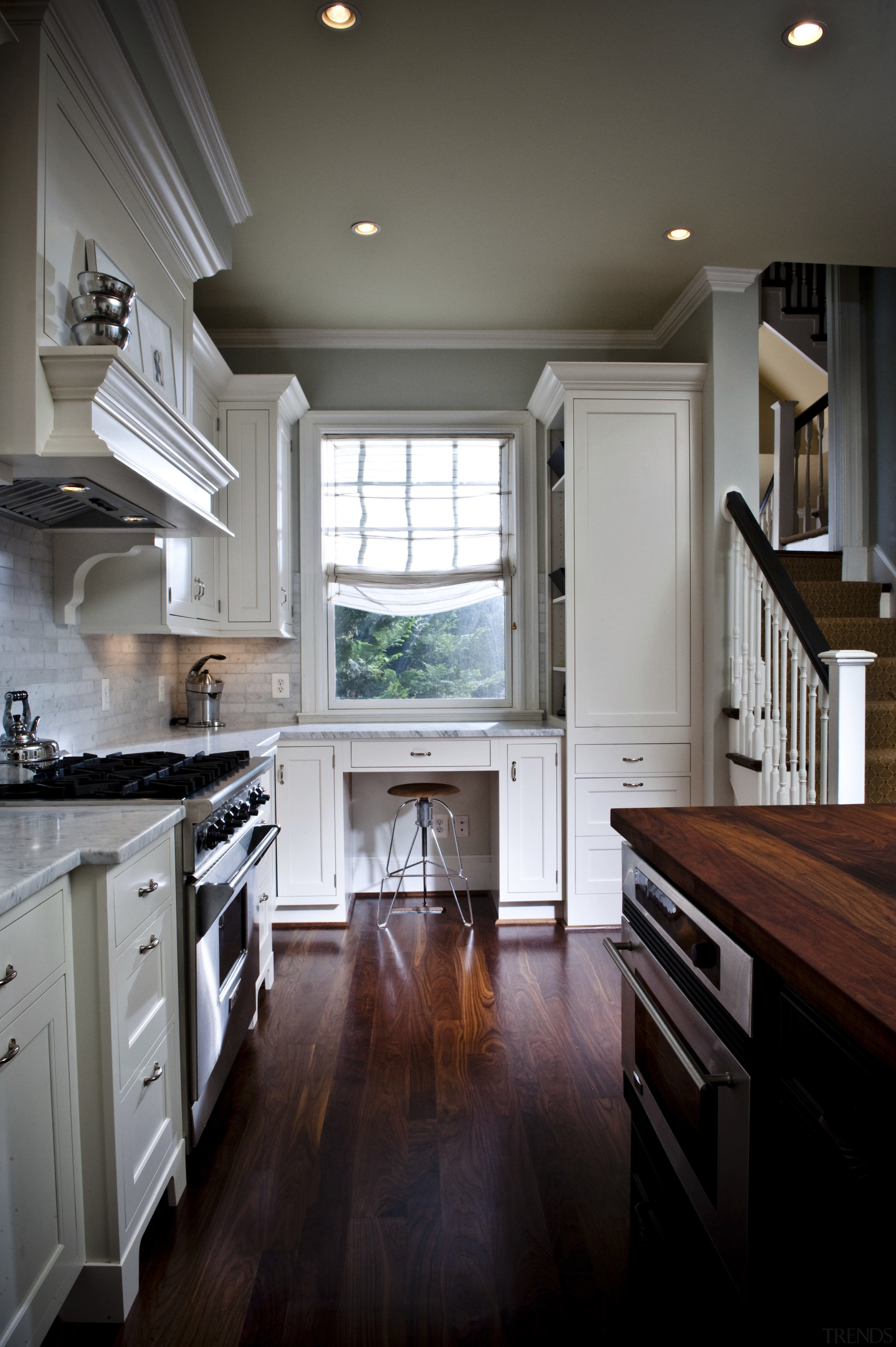 View of kitchen designed by Nadia Subaran. Designed cabinetry, ceiling, countertop, cuisine classique, floor, flooring, hardwood, home, interior design, kitchen, room, under cabinet lighting, window, wood, wood flooring, black, gray