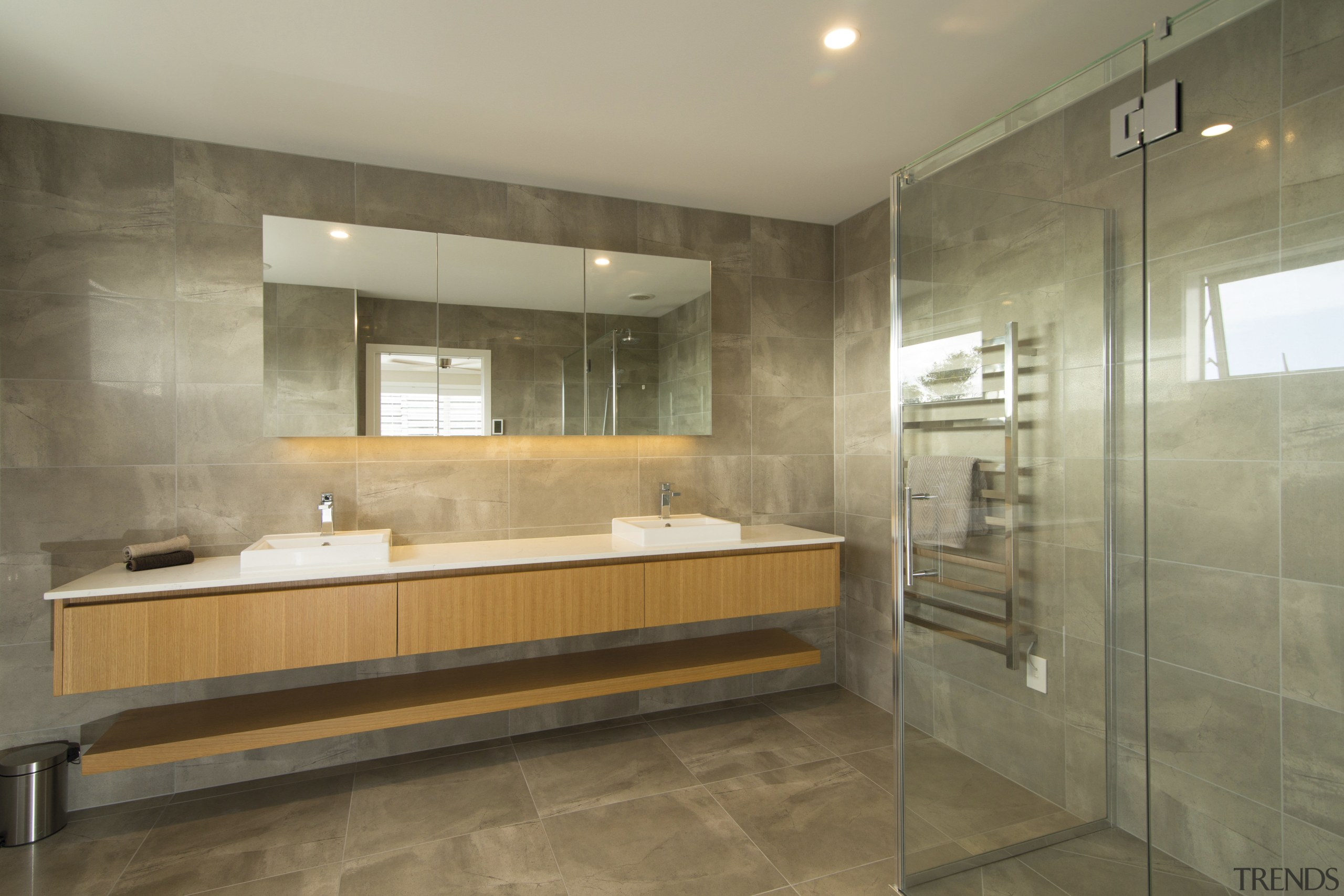 The use of large floor-to-ceiling tiles creates a bathroom, floor, flooring, interior design, real estate, room, tile, brown, orange