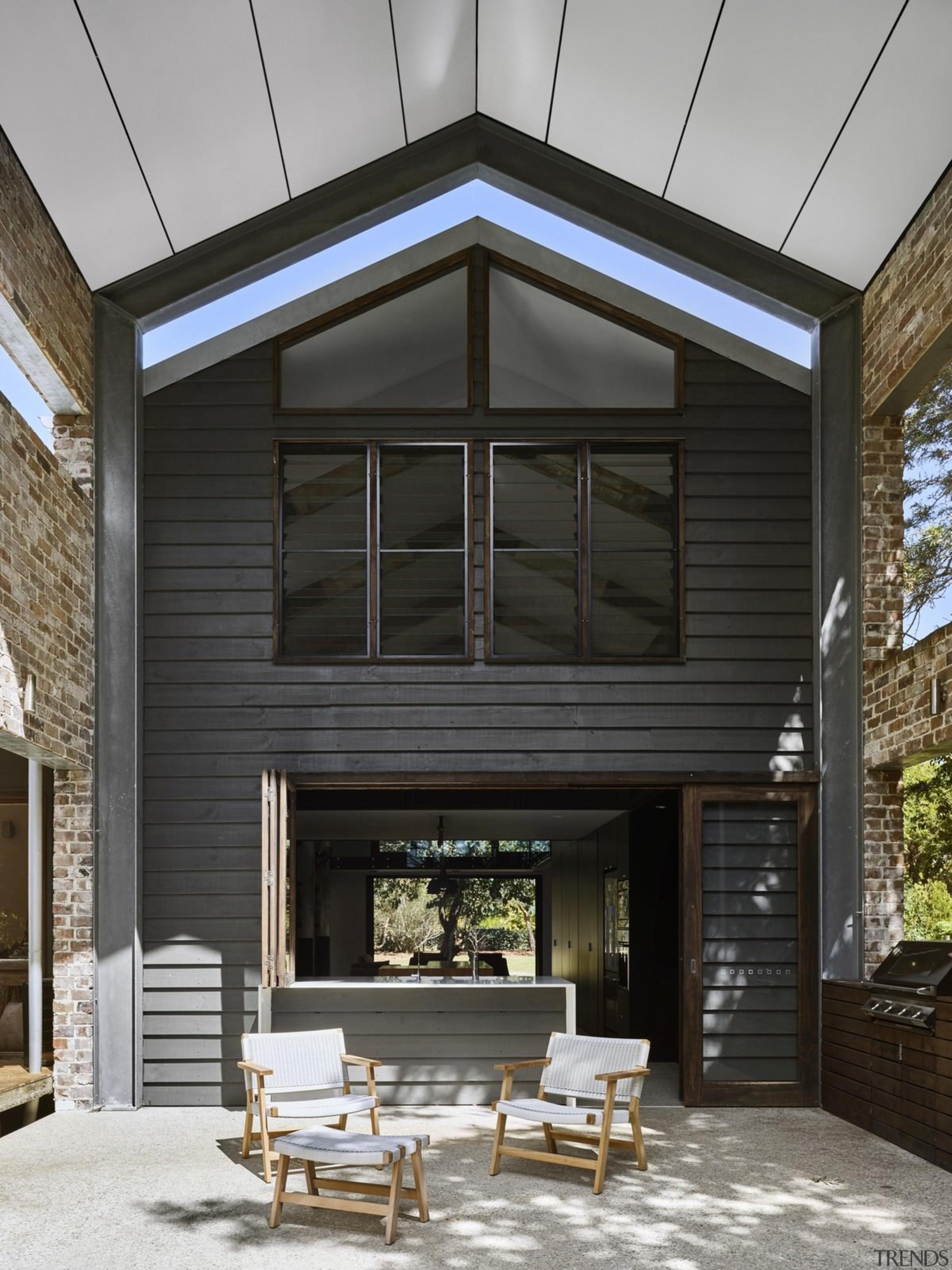 A view of the outdoor room - A facade, home, house, interior design, residential area, siding, window, black, gray
