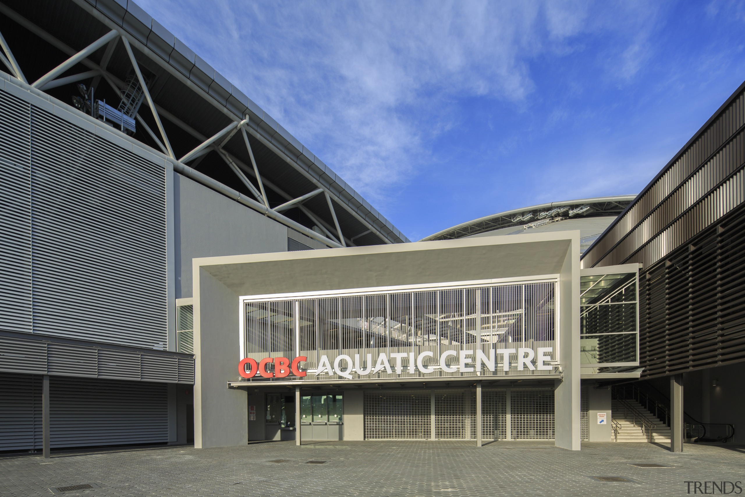 The OCBC Aquatic Centre, by Arup Associates, has architecture, building, commercial building, corporate headquarters, facade, headquarters, mixed use, real estate, structure, black, gray, blue