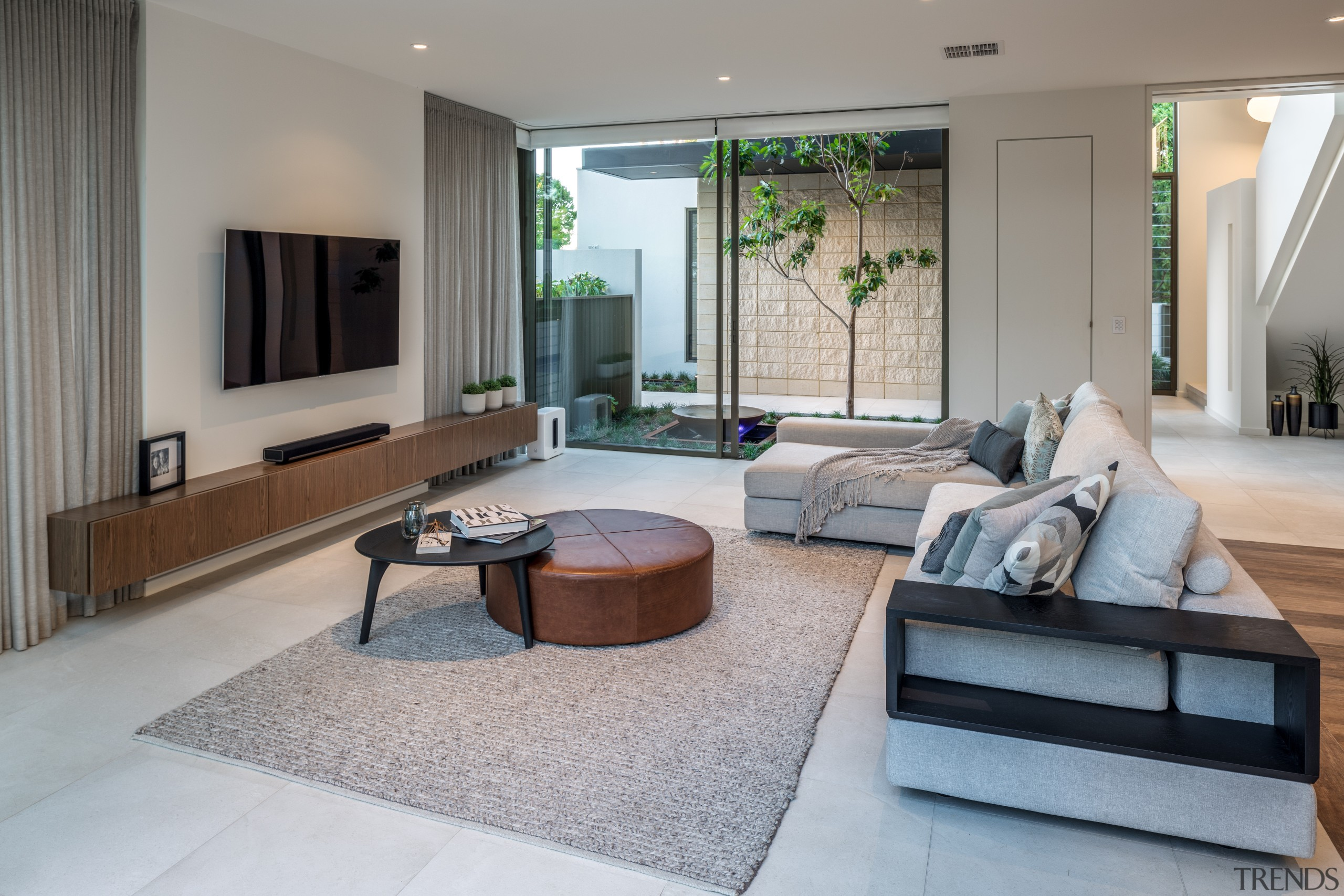 In a home that's all about connections, this apartment, architecture, building, ceiling, coffee table, estate, floor, flooring, furniture, home, house, interior design, living room, lobby, property, real estate, room, table, tile, gray