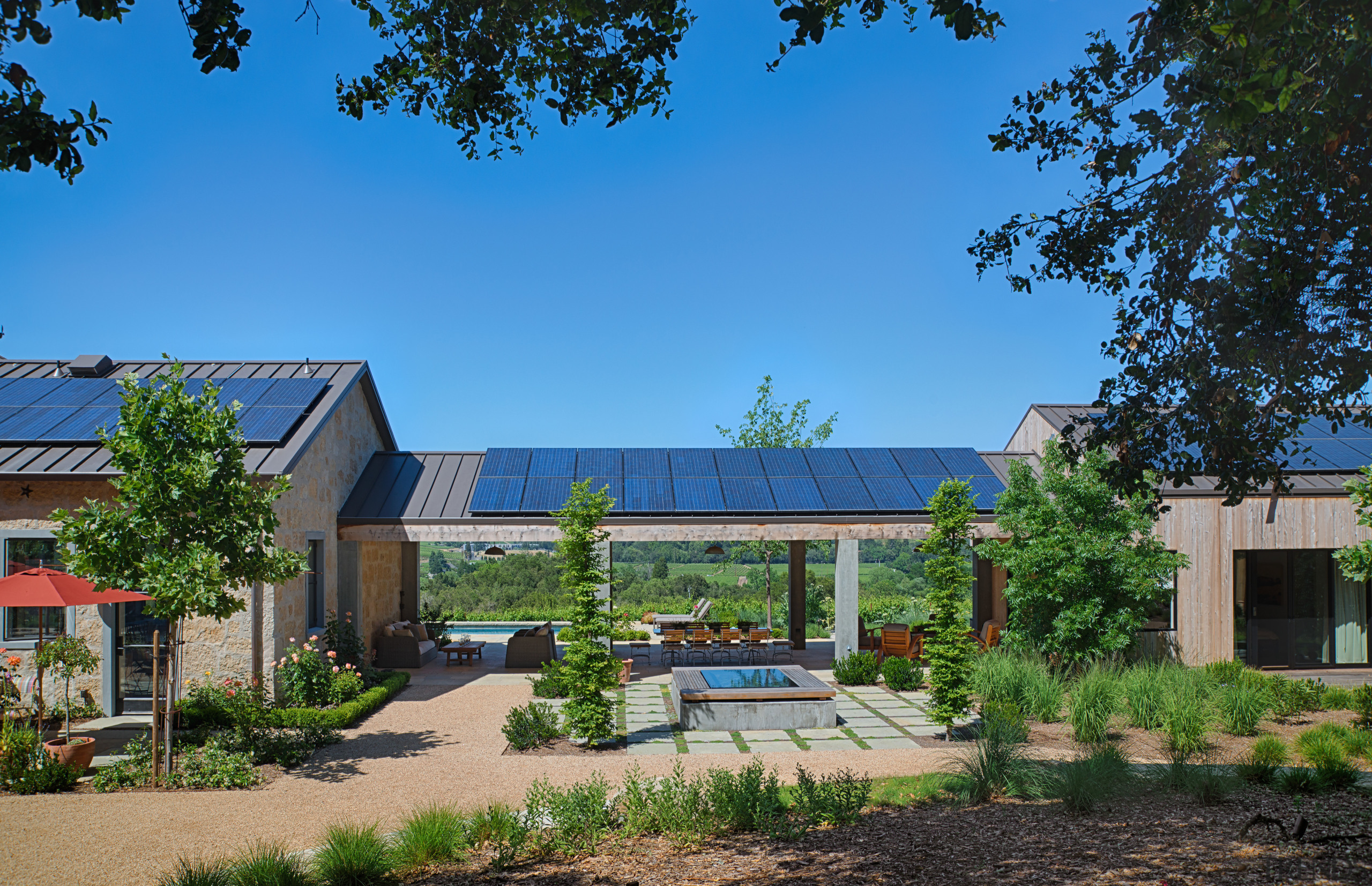 Solar panels on the single storey buildings provide cottage, estate, home, house, plant, property, real estate, residential area, roof, sky, suburb, tree, teal