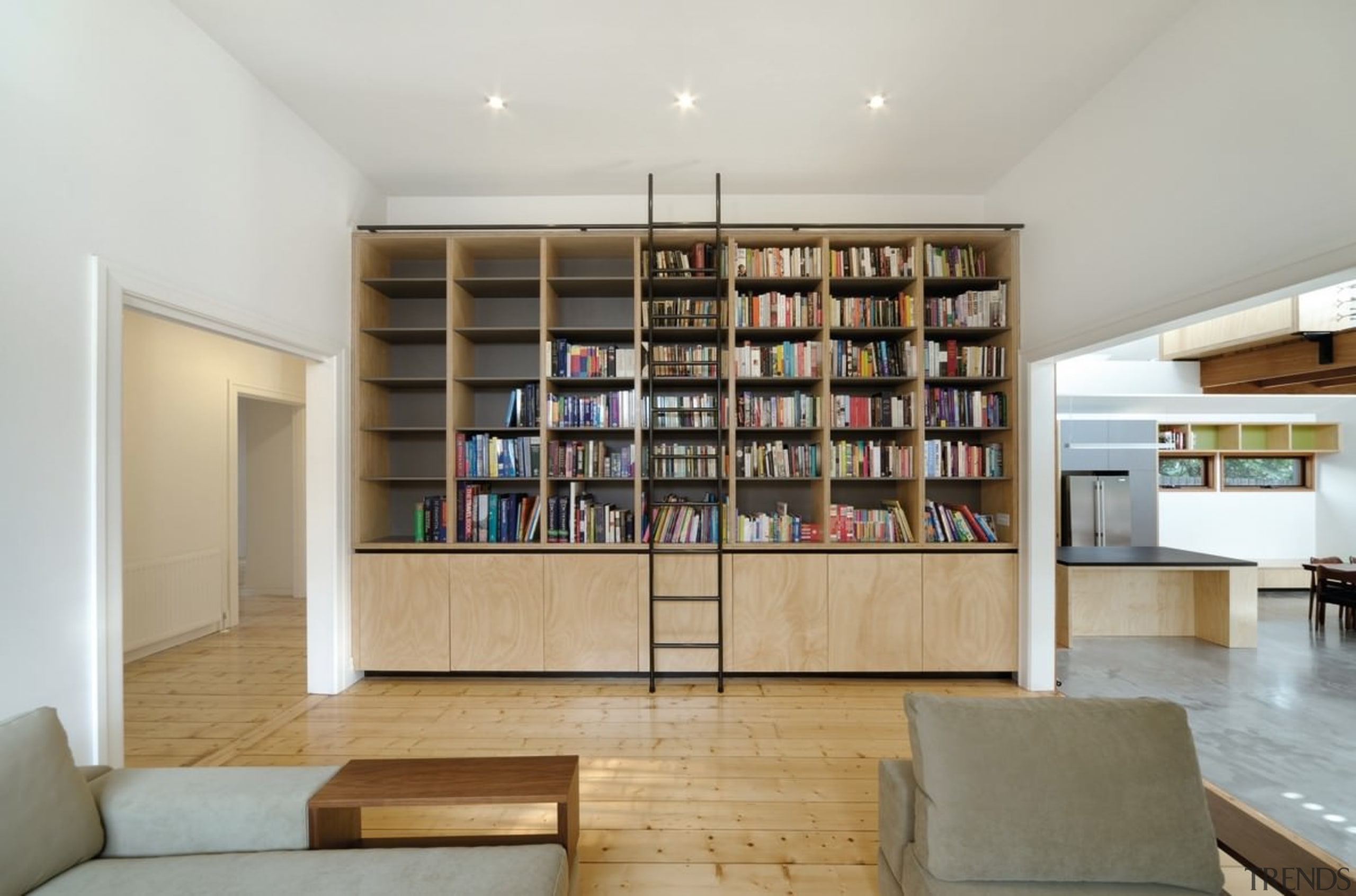 A Large Bookshelf Separates The Hallway And Living Area