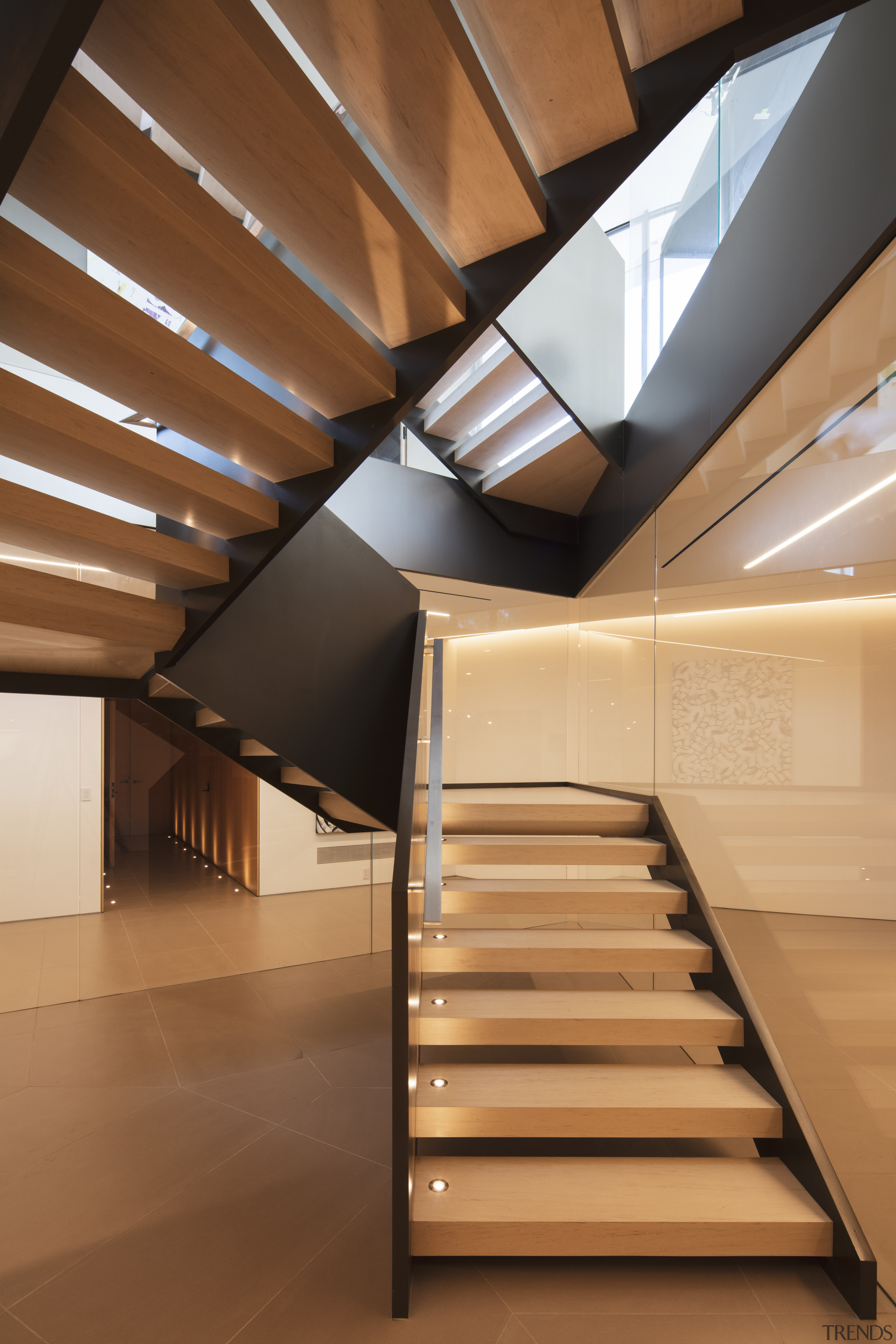 A prominent staircase runs through the central point architecture, building, ceiling, daylighting, floor, handrail, house, interior design, line, loft, room, stairs, window, brown, orange