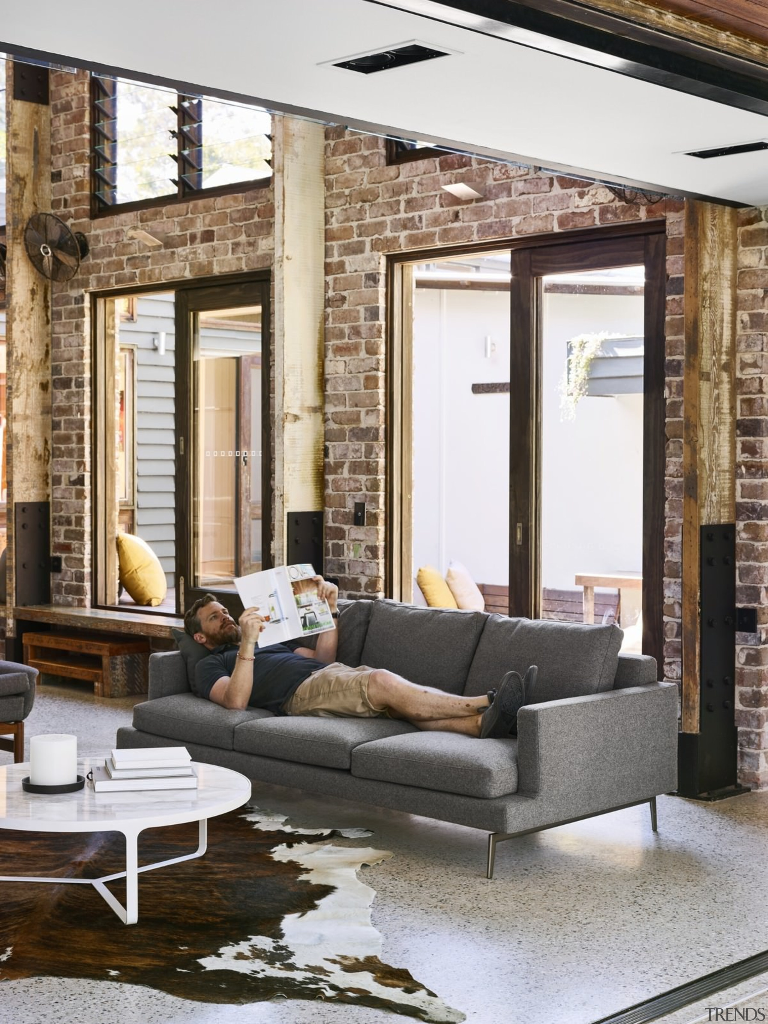 The brick from the workers cottage remains in ceiling, chair, couch, floor, furniture, home, interior design, living room, loft, loveseat, table, wall, window, white