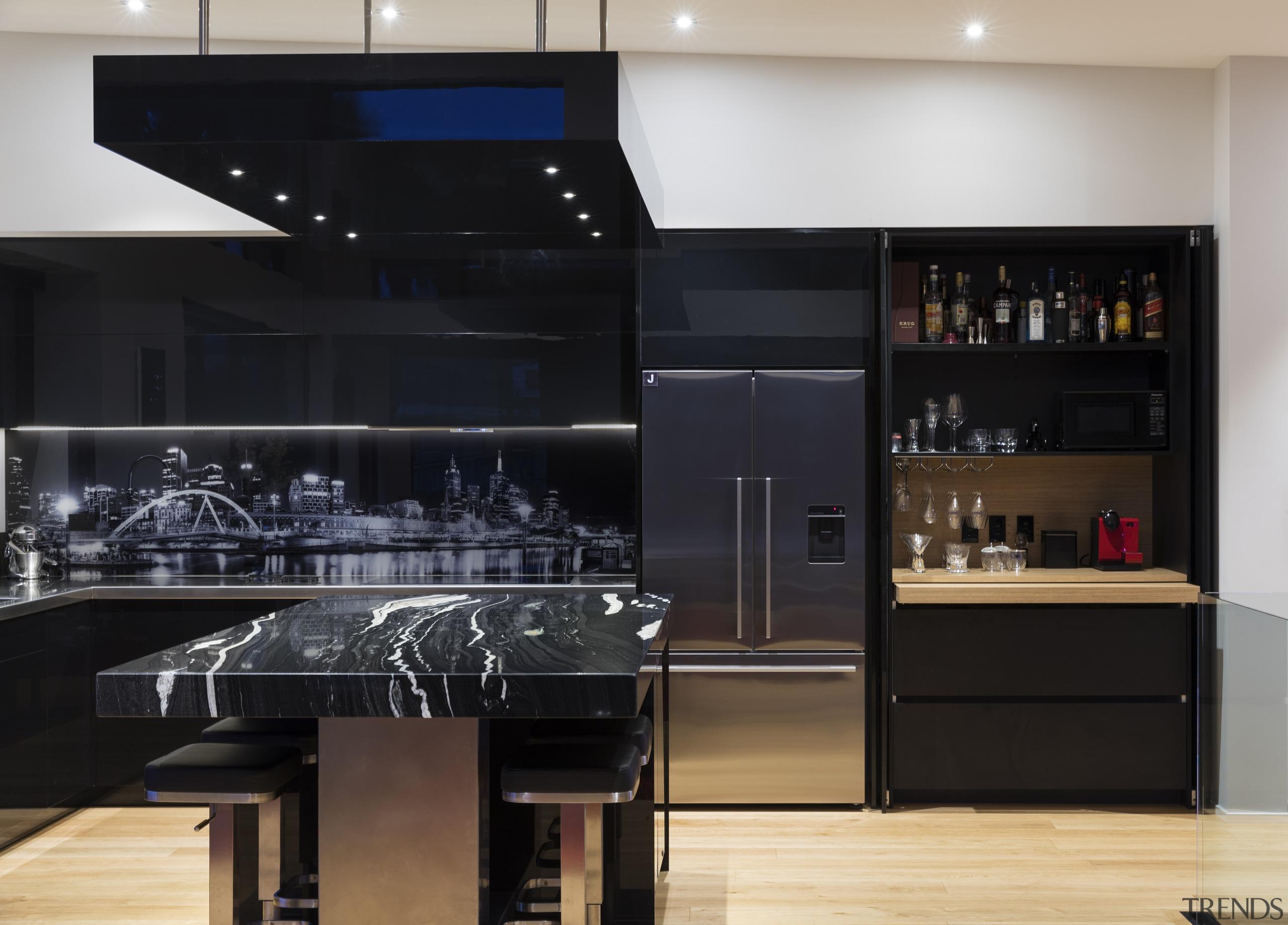 A suspended bulkhead over the island utilises the cabinetry, countertop, interior design, kitchen, black