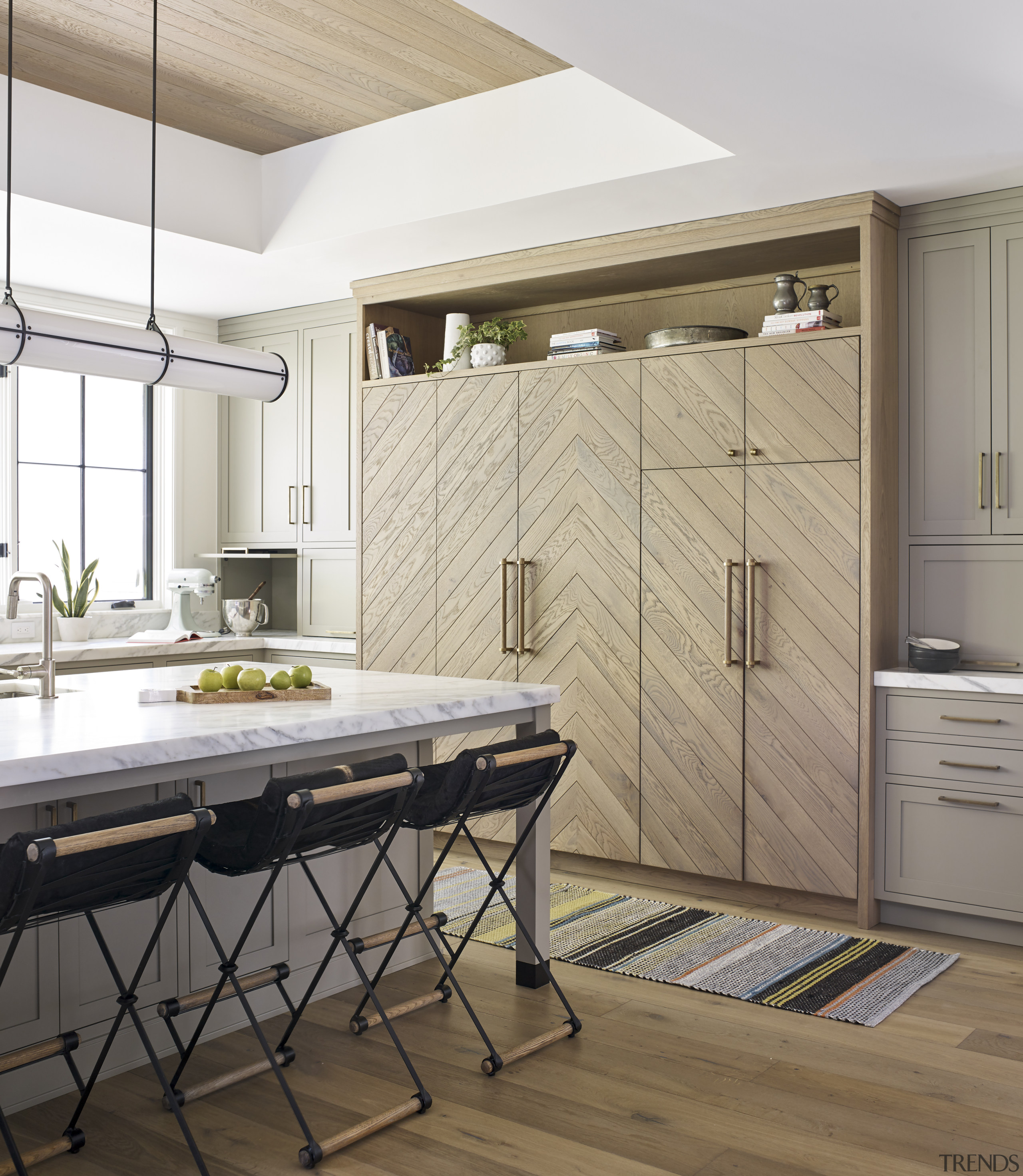 In this kitchen, classic paneled down-to-counter cabinetry hides