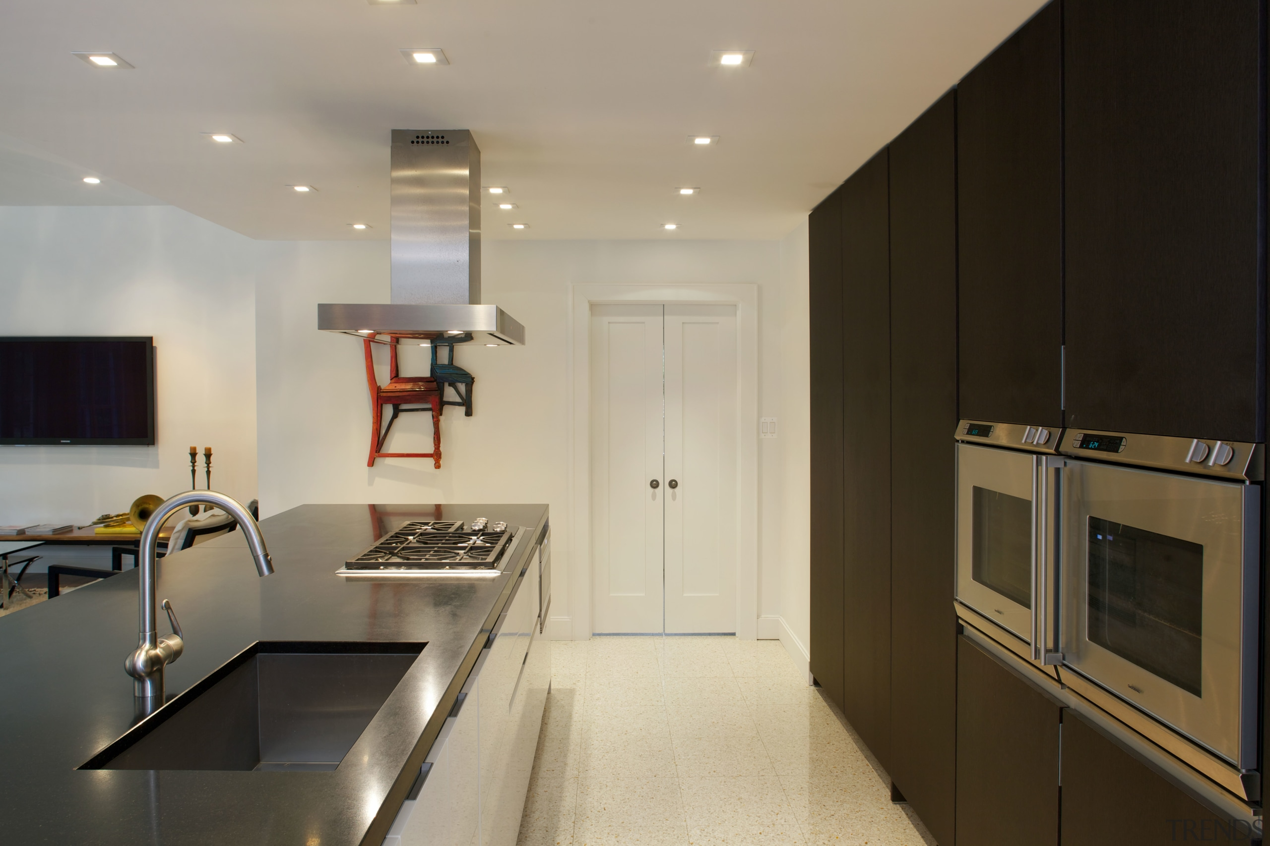 This new kitchen features a long island with cabinetry, countertop, home appliance, interior design, kitchen, real estate, room, orange, black