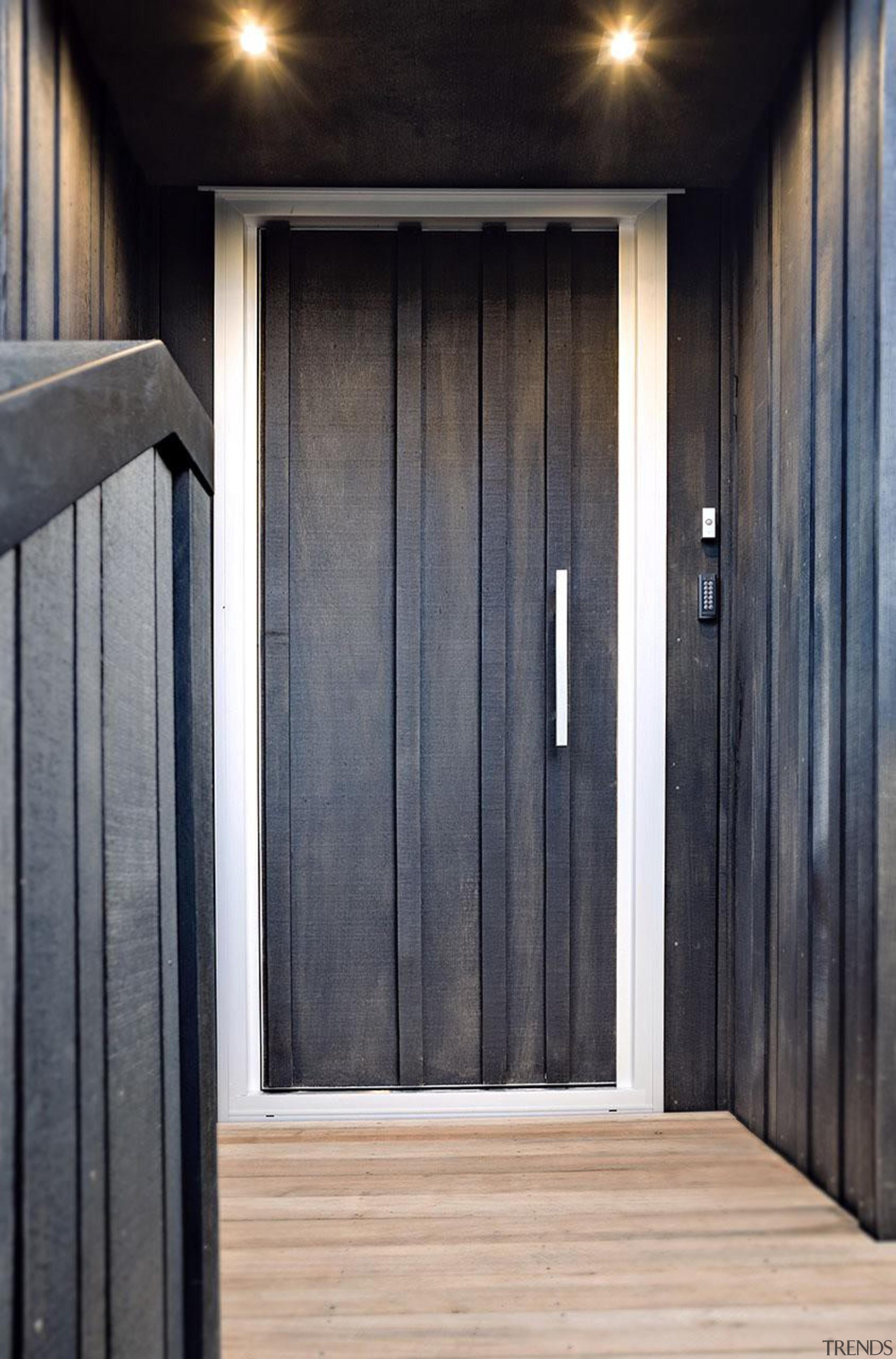 The custom front door melds into the exterior door, floor, hardwood, home, house, wall, window, wood, wood stain, gray, black