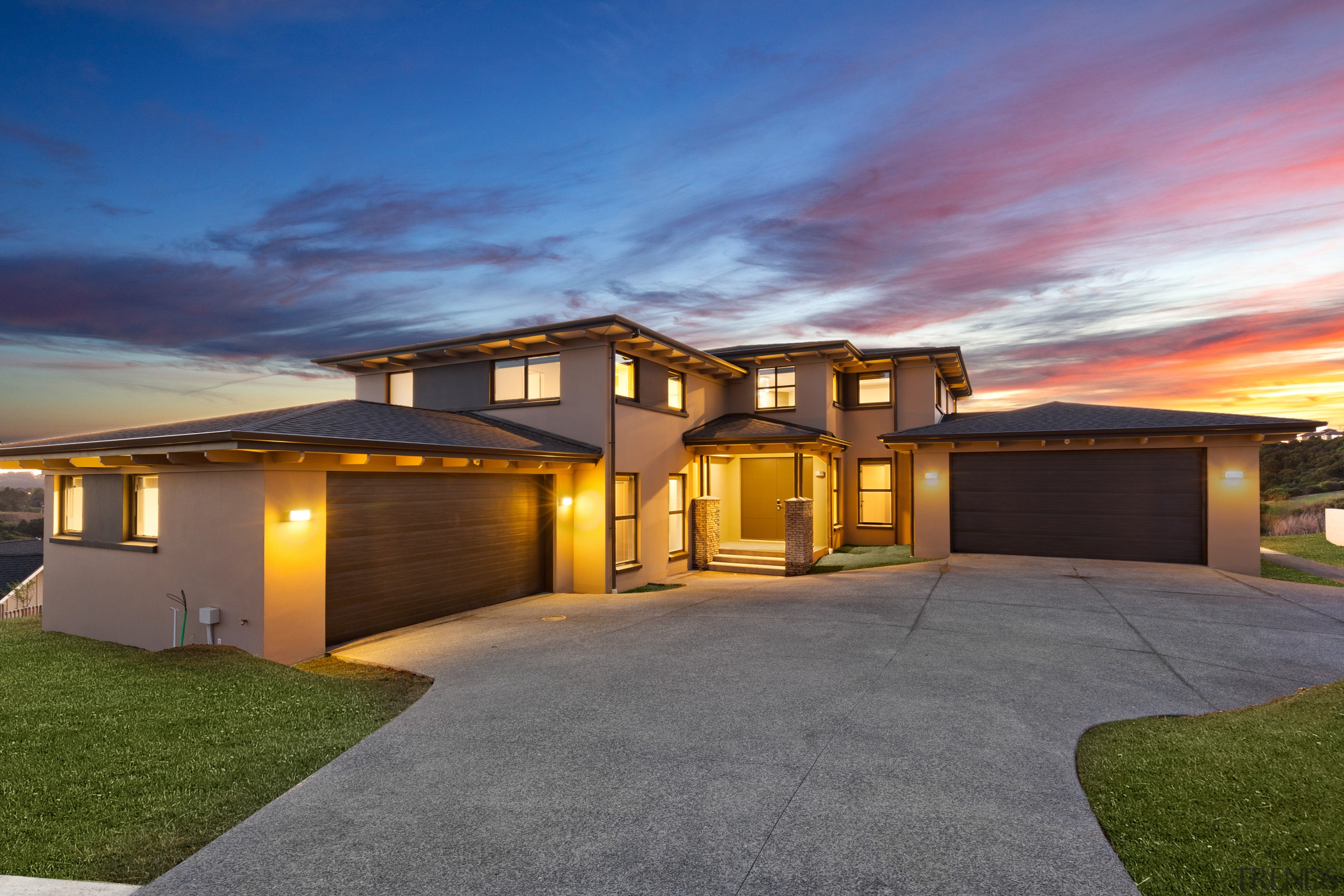 Two levels at entry, this generous-sized house by architecture, backyard, building, concrete, design, door, driveway, estate, facade, grass, home, house, interior design, land lot, landscape, landscaping, lighting, mansion, property, real estate, residential area, roof, sky, suburb, gray