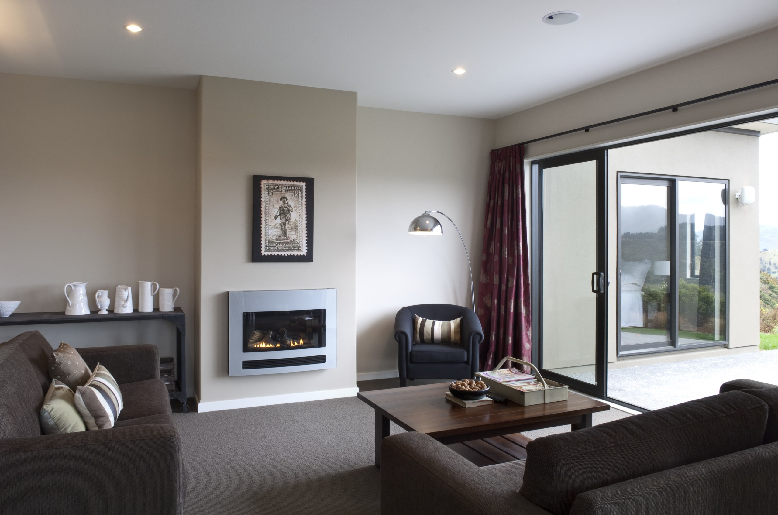 This Upper Hutt Show home was designed and ceiling, floor, flooring, hearth, home, interior design, living room, property, real estate, room, suite, window, gray, white, black