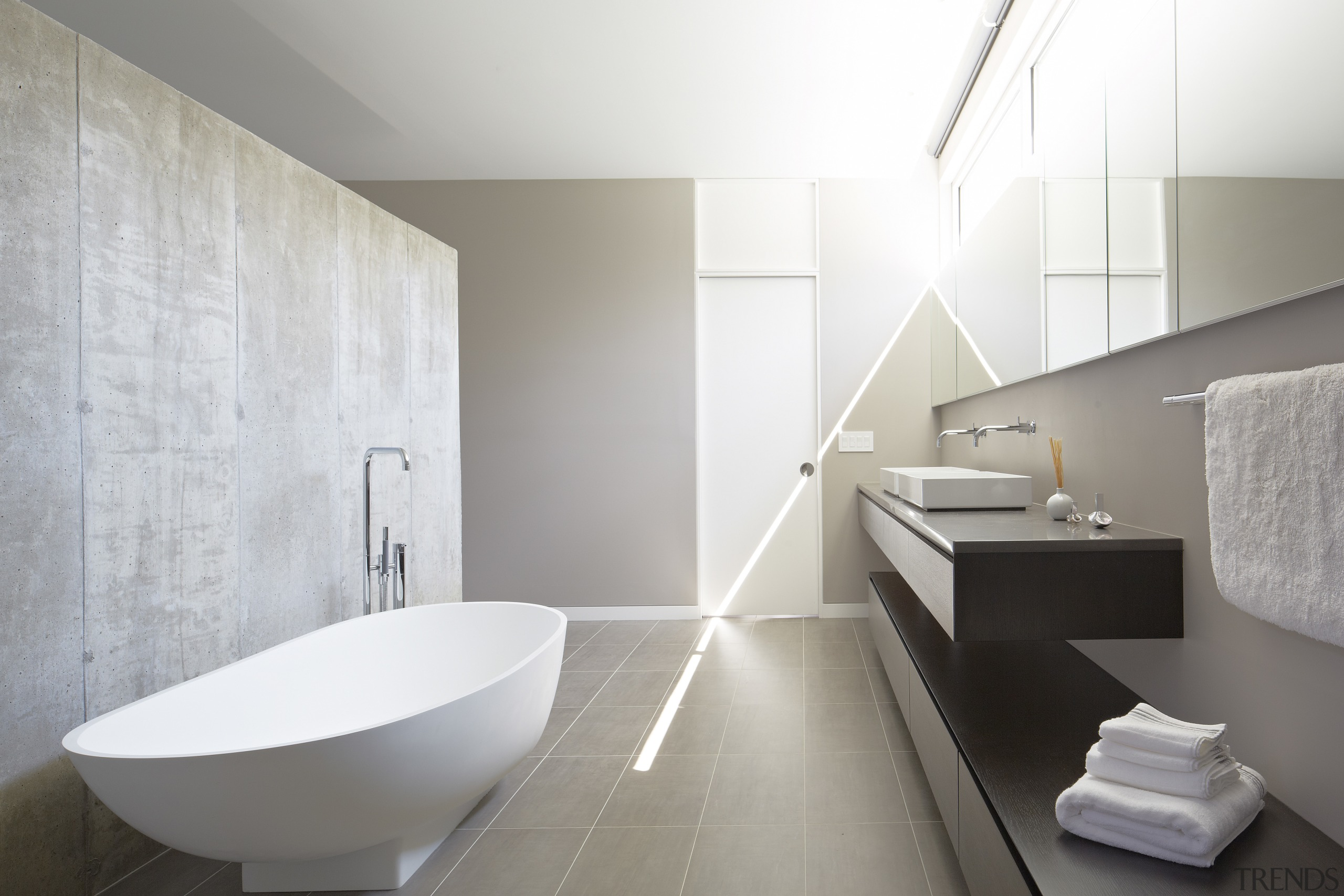 In this master bathroom by Studio Dwell, clerestory architecture, bathroom, bathroom sink, bidet, ceramic, floor, interior design, plumbing fixture, product design, room, sink, tap, tile, wall, white, gray