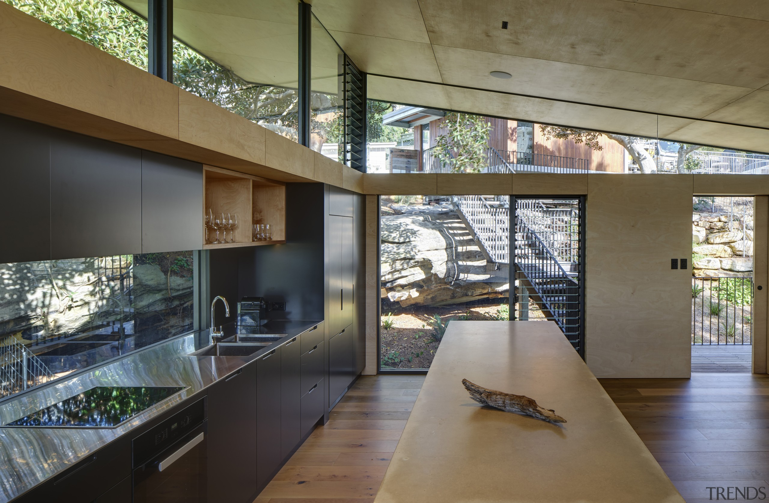 The kitchen, with window splashback, opens up to