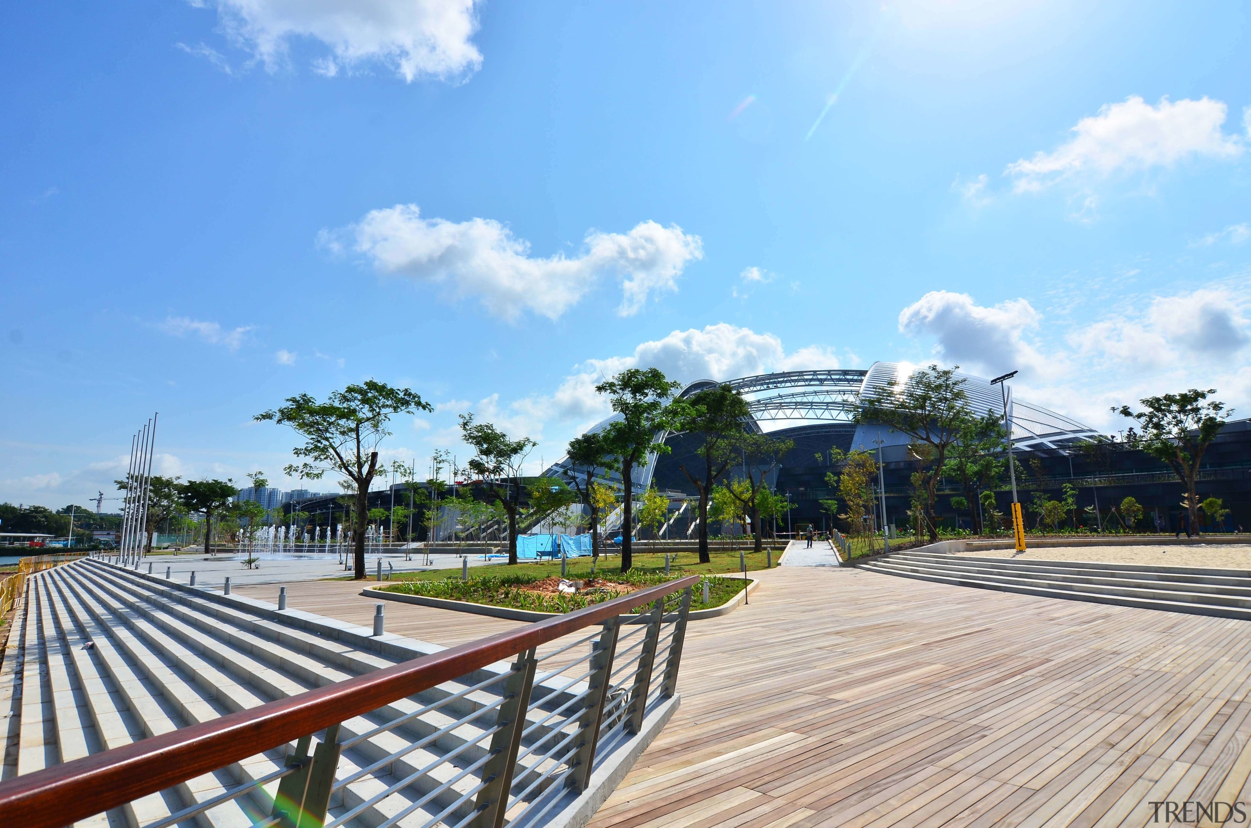 Public amenities at the Singapore Sports Hub include area, boardwalk, cloud, estate, leisure, real estate, recreation, residential area, sky, tree, walkway, teal