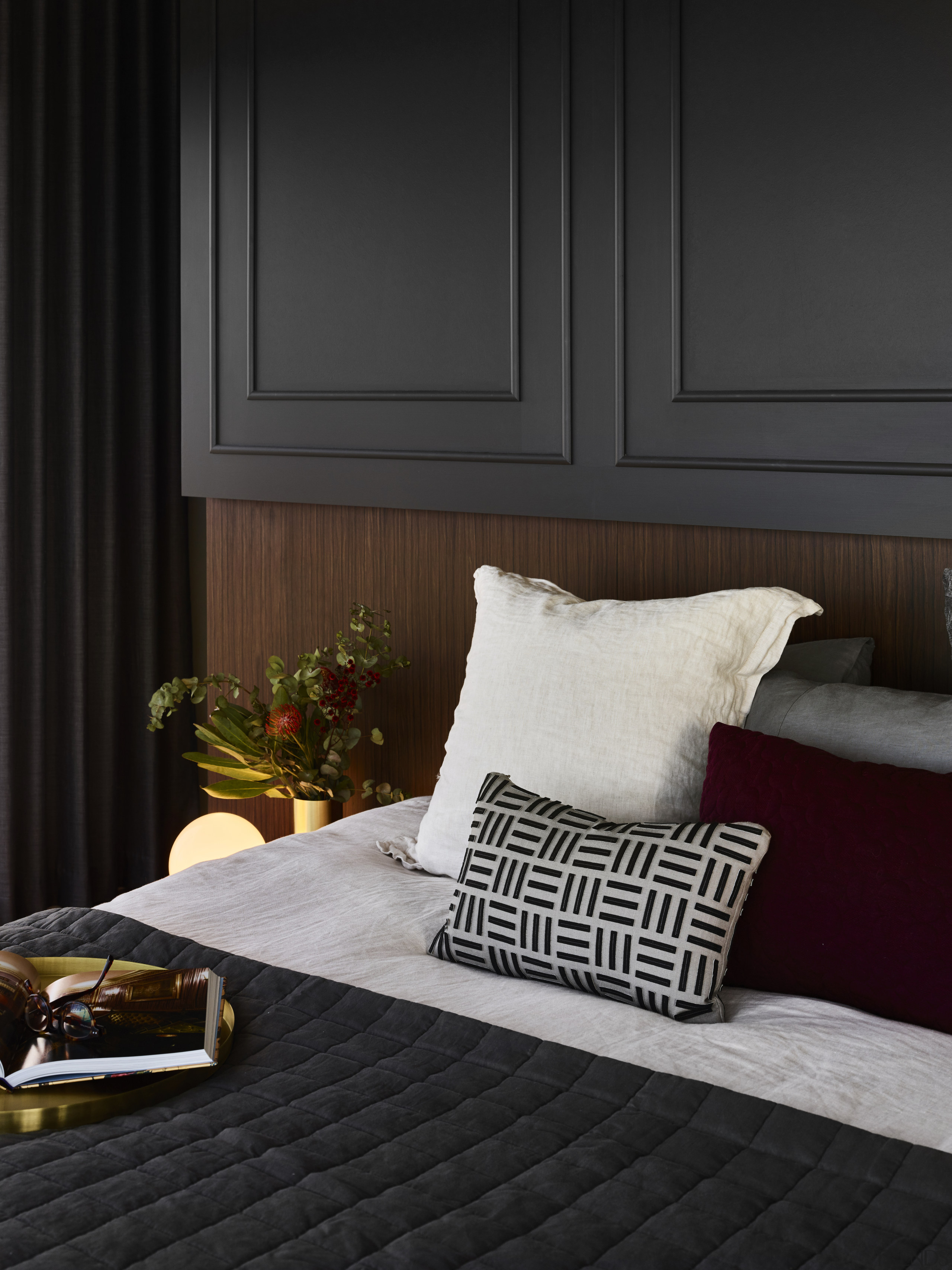 The sense of masculine opulence seen in the bed, bed frame, bed sheet, bedding, bedroom, couch, design, duvet cover, floor, fur, furniture, hardwood, house, interior design, linens, pillow, room, textile, wall, wood, black