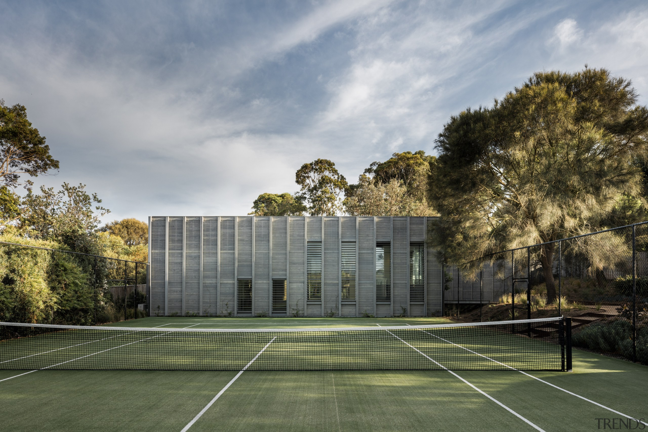 For this understated guest house, automated shutters provide architecture, area, building, campus, cloud, corporate headquarters, daytime, estate, grass, home, house, landscape, plant, real estate, residential area, sky, sport venue, structure, sunlight, tree, gray