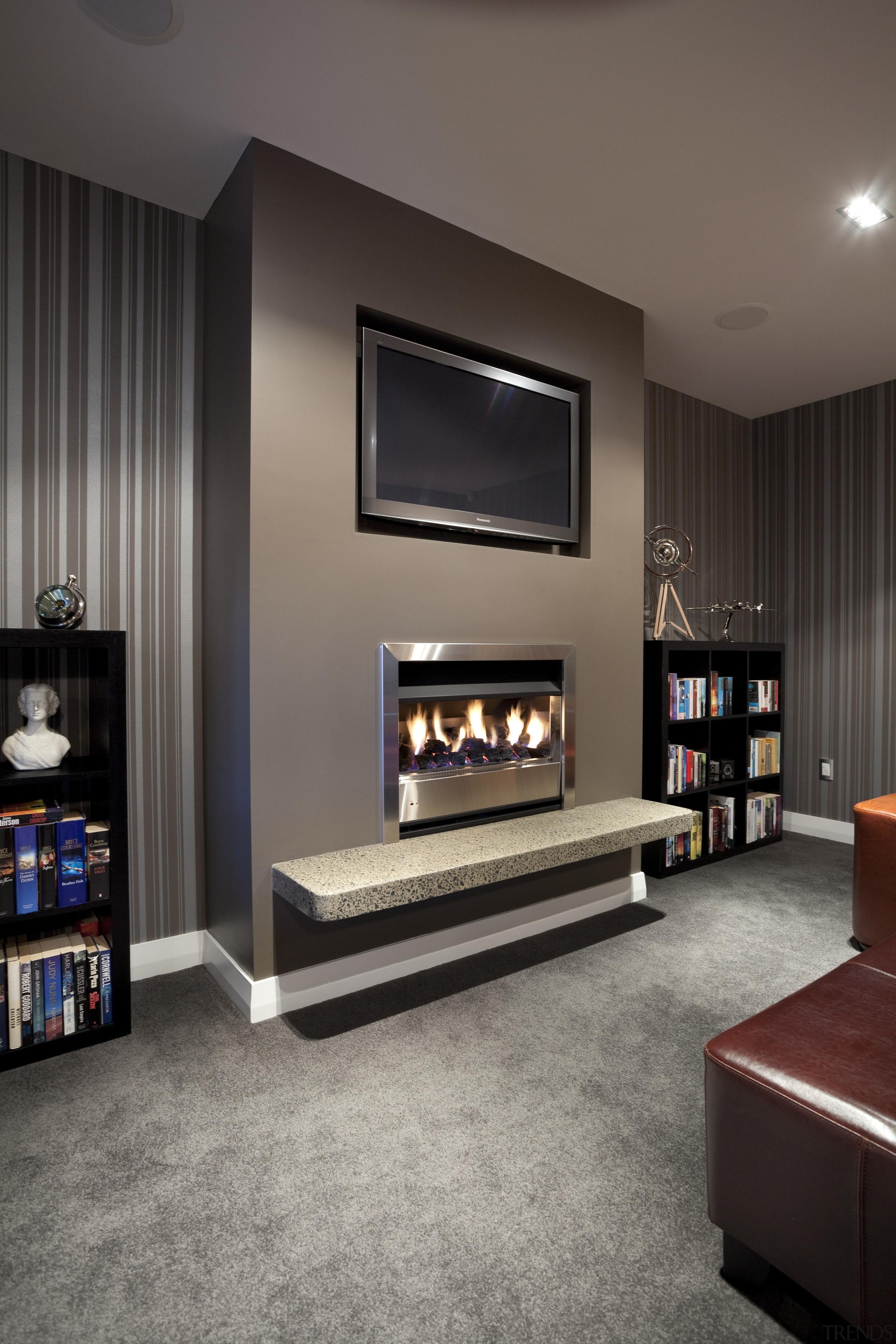 tv screen above fireplace in dark wallpapered room fireplace, floor, flooring, furniture, hearth, interior design, living room, room, gray, black
