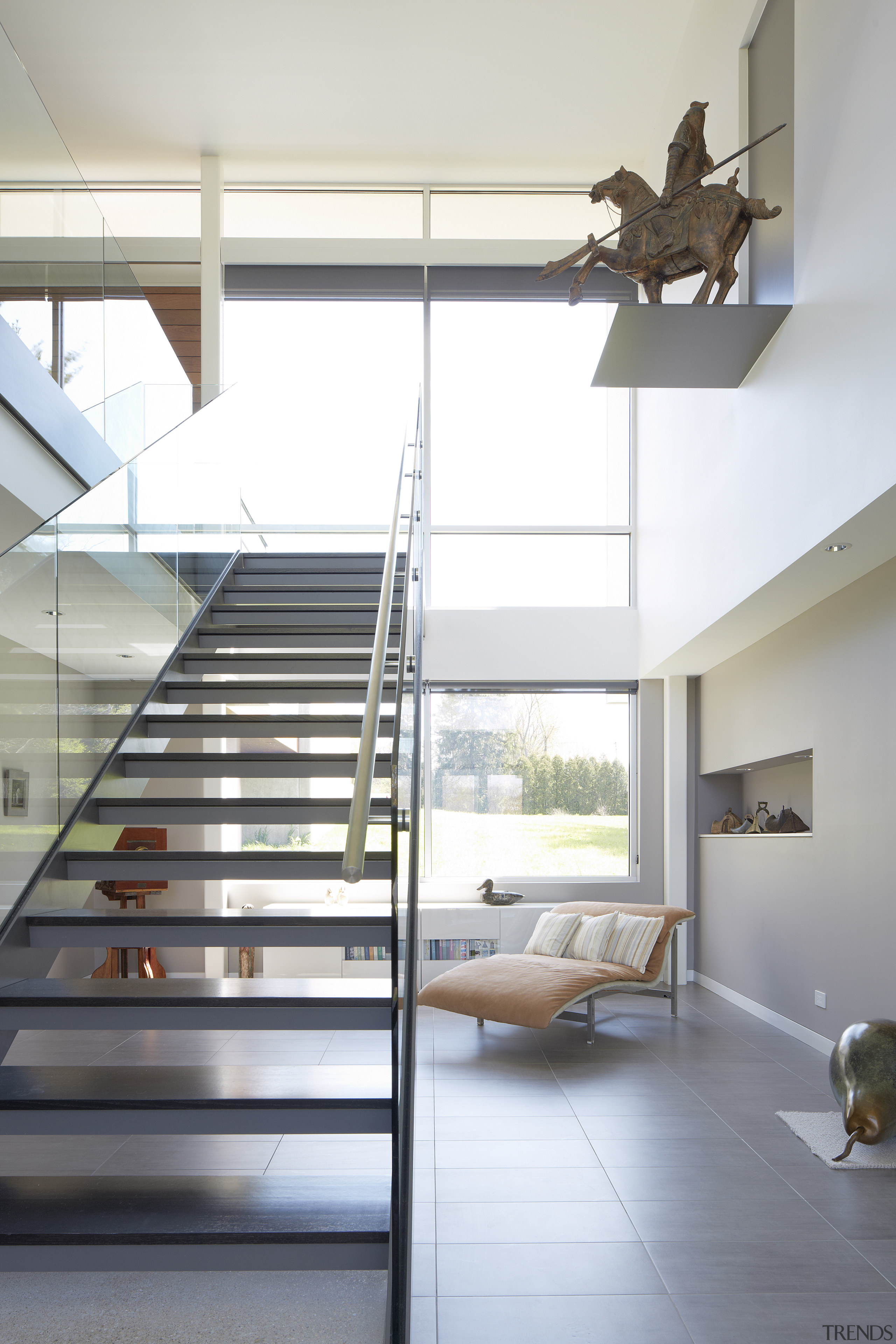 A double-height void adds drama and transparency to architecture, daylighting, floor, handrail, home, house, interior design, loft, product design, stairs, white, gray