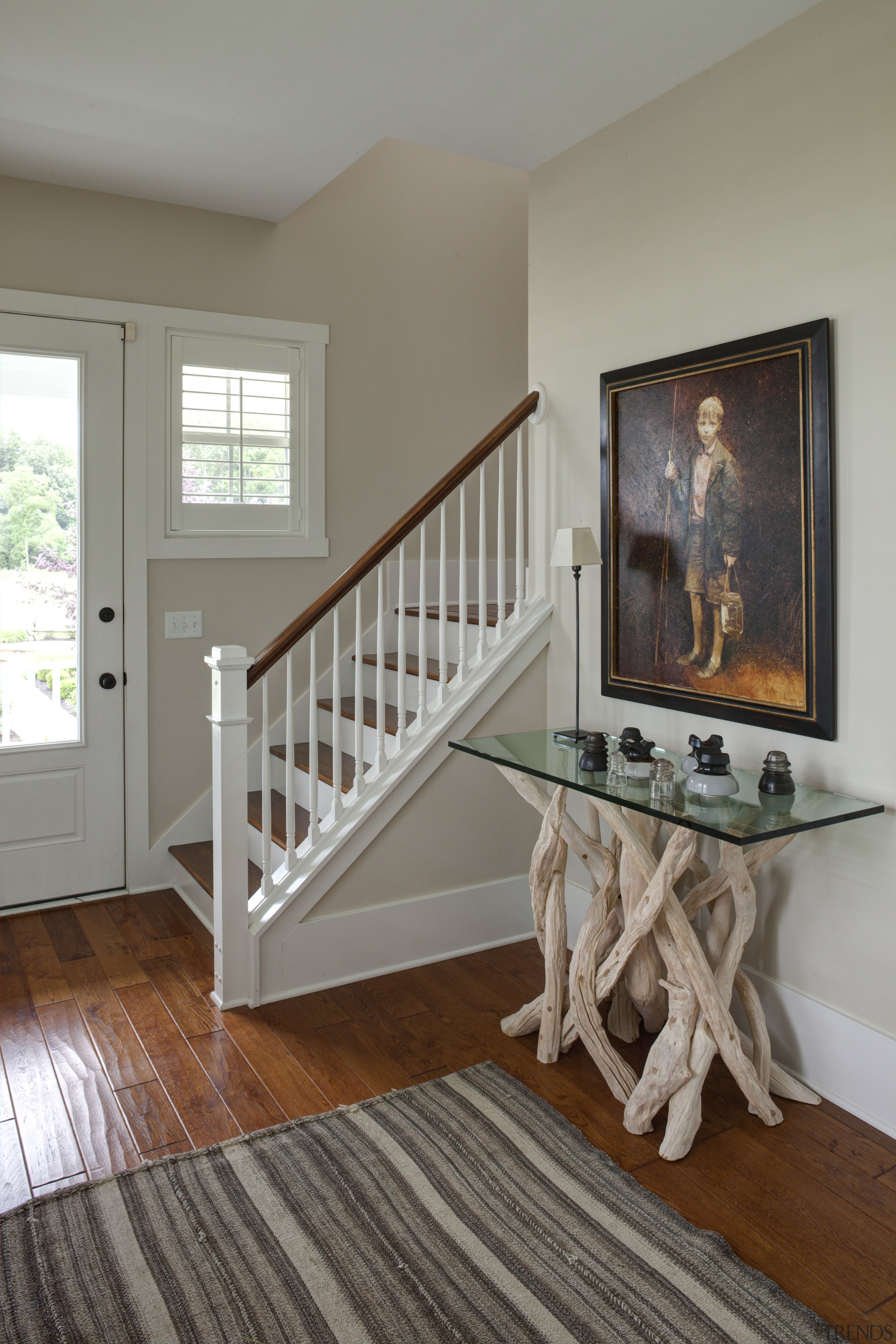 A stairway in the front entry of a baluster, bed, bed frame, floor, flooring, furniture, handrail, hardwood, home, house, interior design, laminate flooring, living room, product, room, stairs, table, wall, window, wood, wood flooring, wood stain, gray