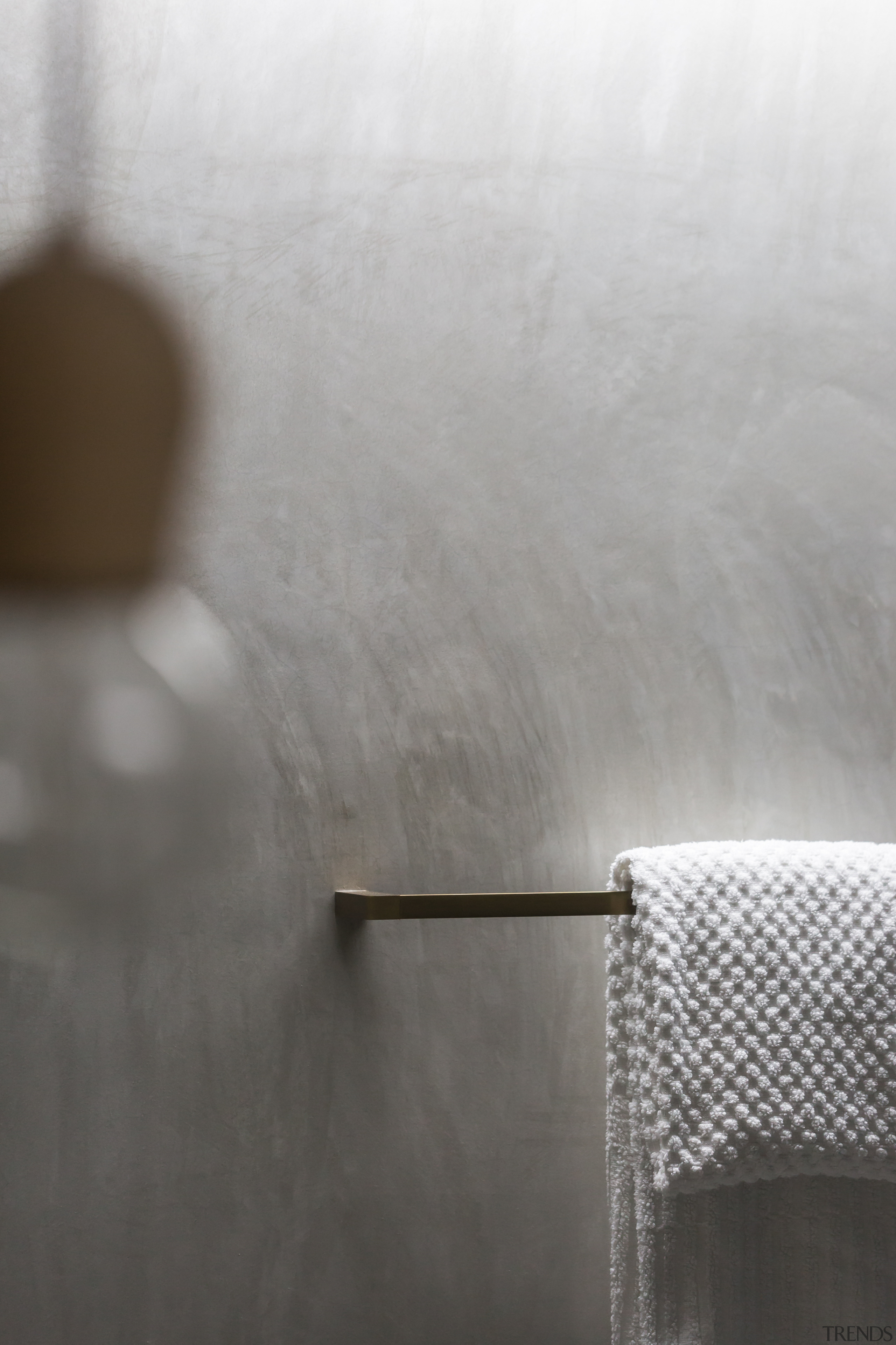 ​​​​​​​Burnished brass accessories bring a rich accent to floor, wall, grey tiles,  Arc Seven, towel rail, brass